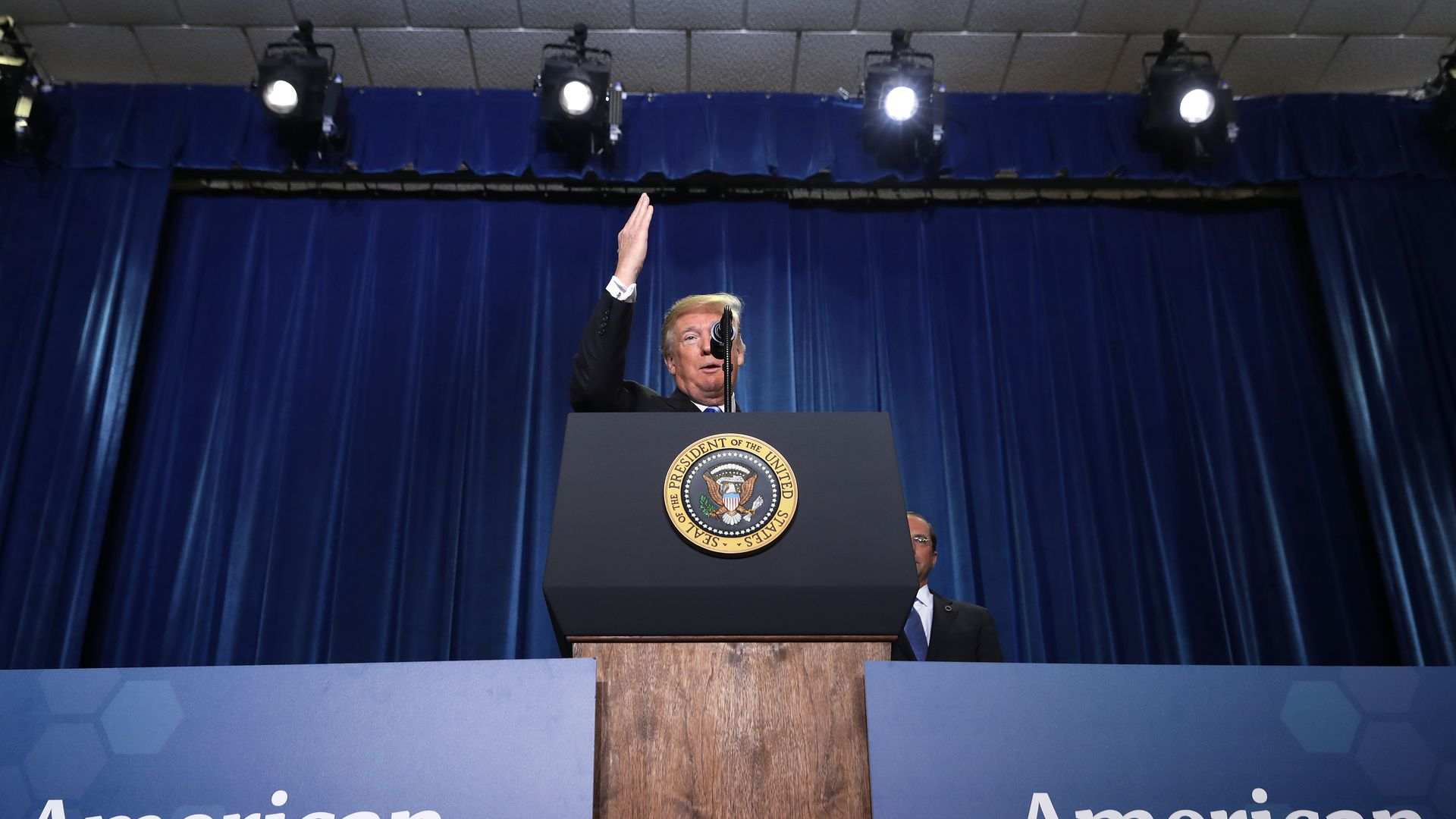 In this image, President Trump speaks behind a podium with the presidential seal on it.