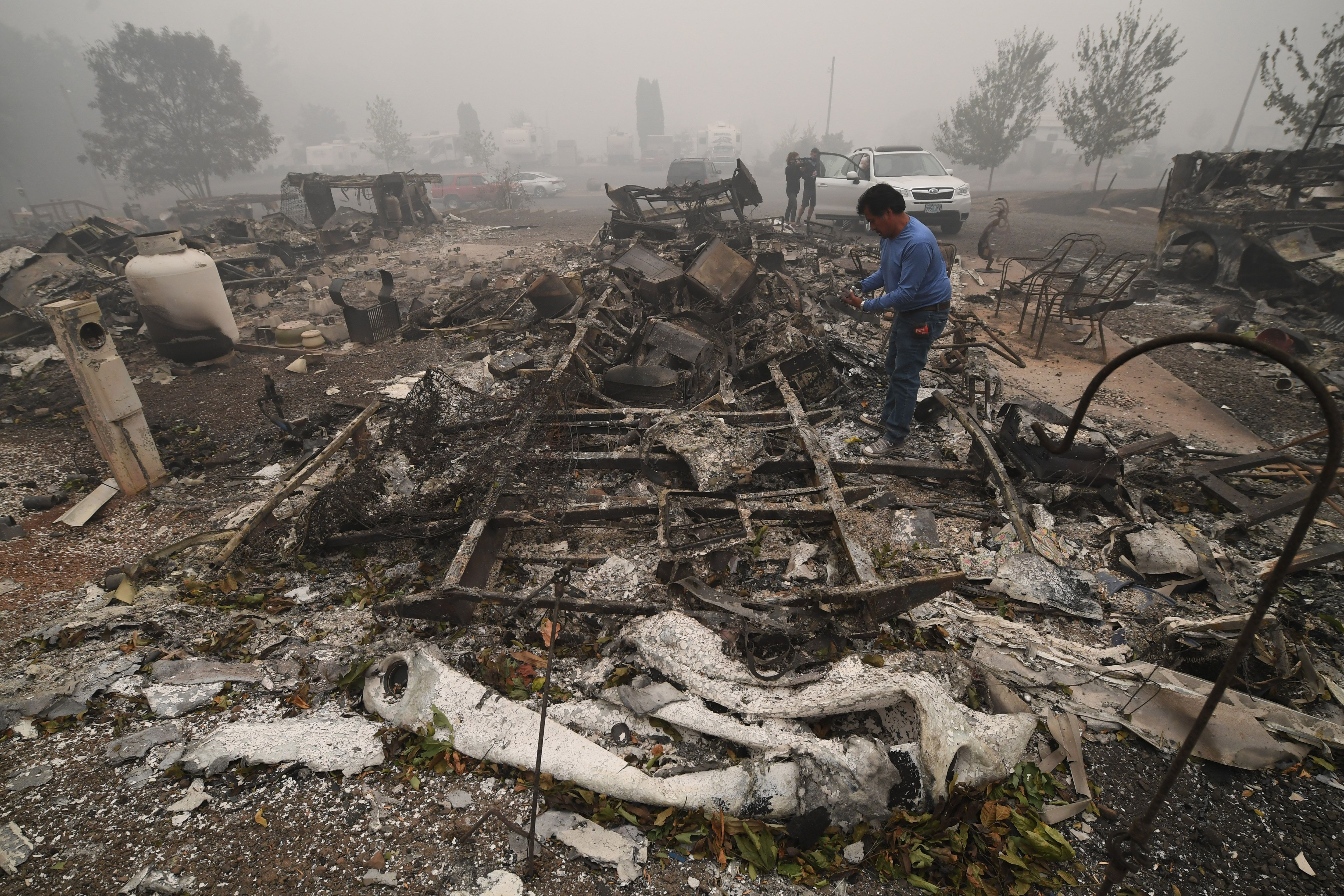 Marcelino Maceda looks for items in the remains of his mobile home after a wildfire swept through the R.V. park destroying multiple homes in Estacada, Oregon September 12
