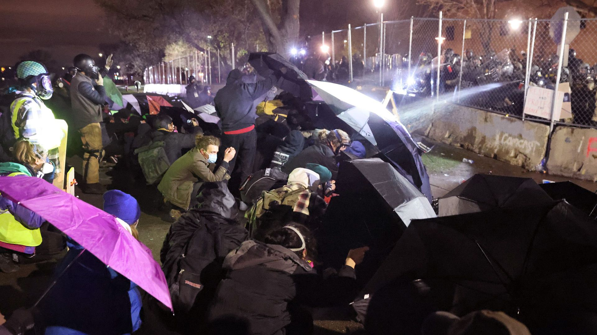 Demonstrators protesting the April 11 death of Wright use umbrellas for protection from pepper spray and rubber bullets outside the police station April 14.