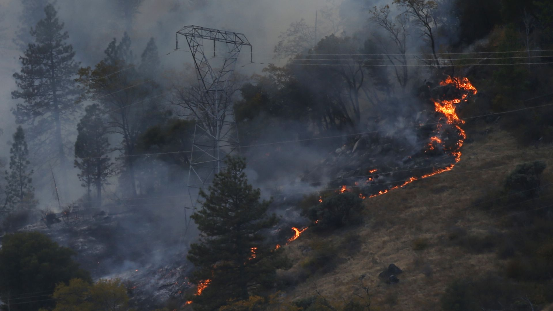 Photo of a transmission tower with a wildfire nearby