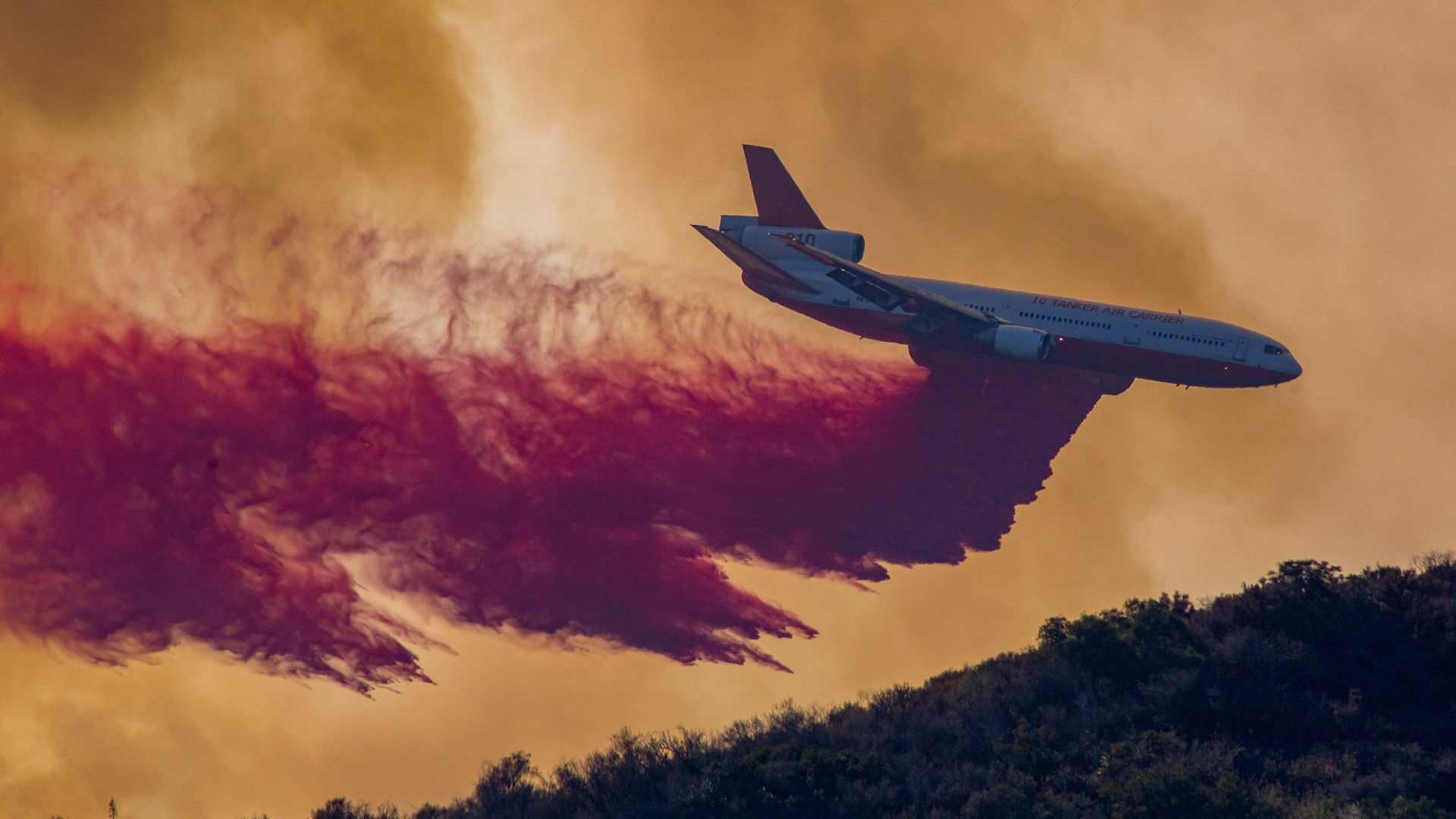 The Tanker Air Carrier DC-10 jet drops fire retardant at the Holy Fire near Lake Elsinore, in Orange County, California, on August 7, 2018.