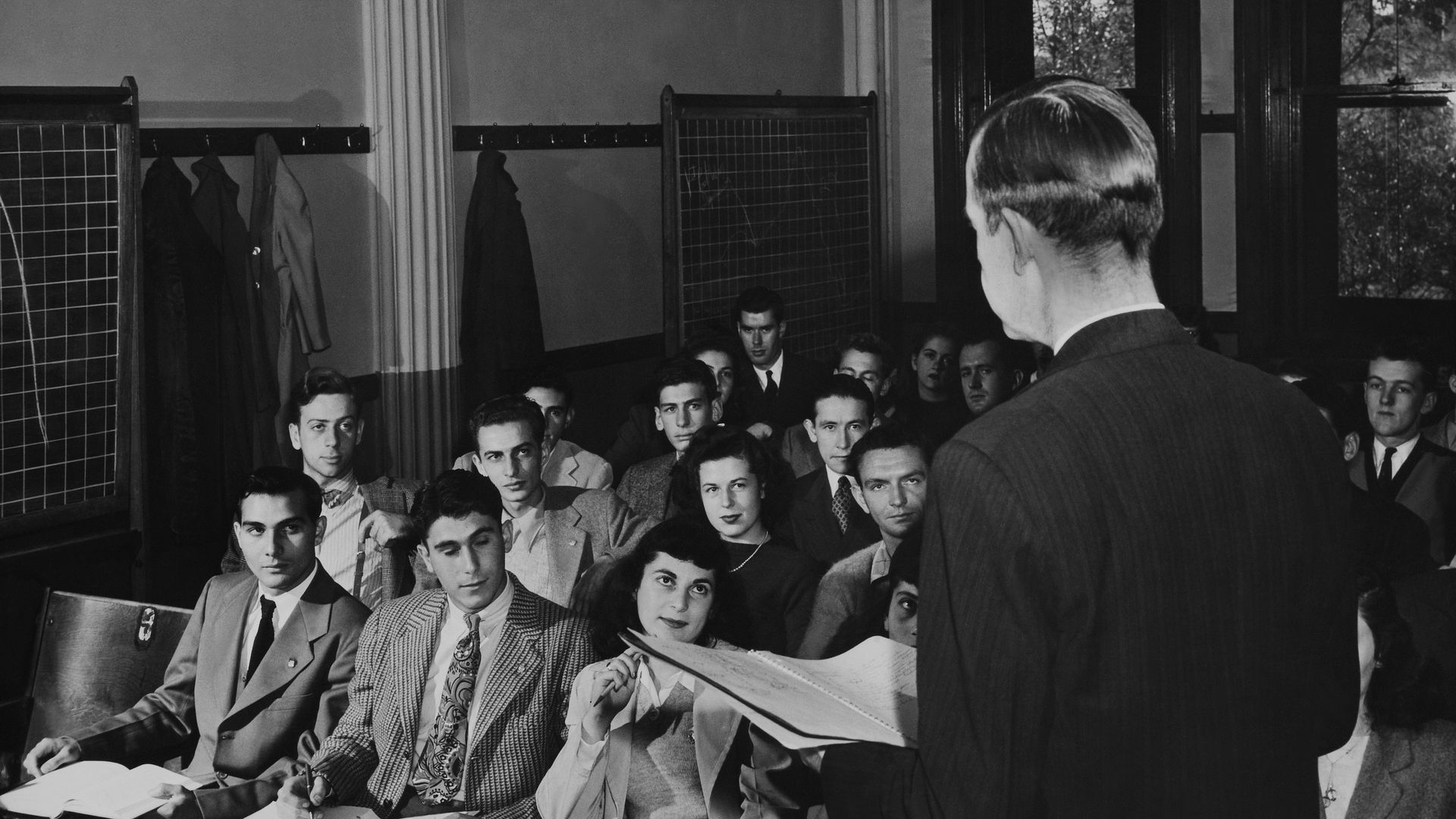 A lecturer stands before rows of students in a black and white photo