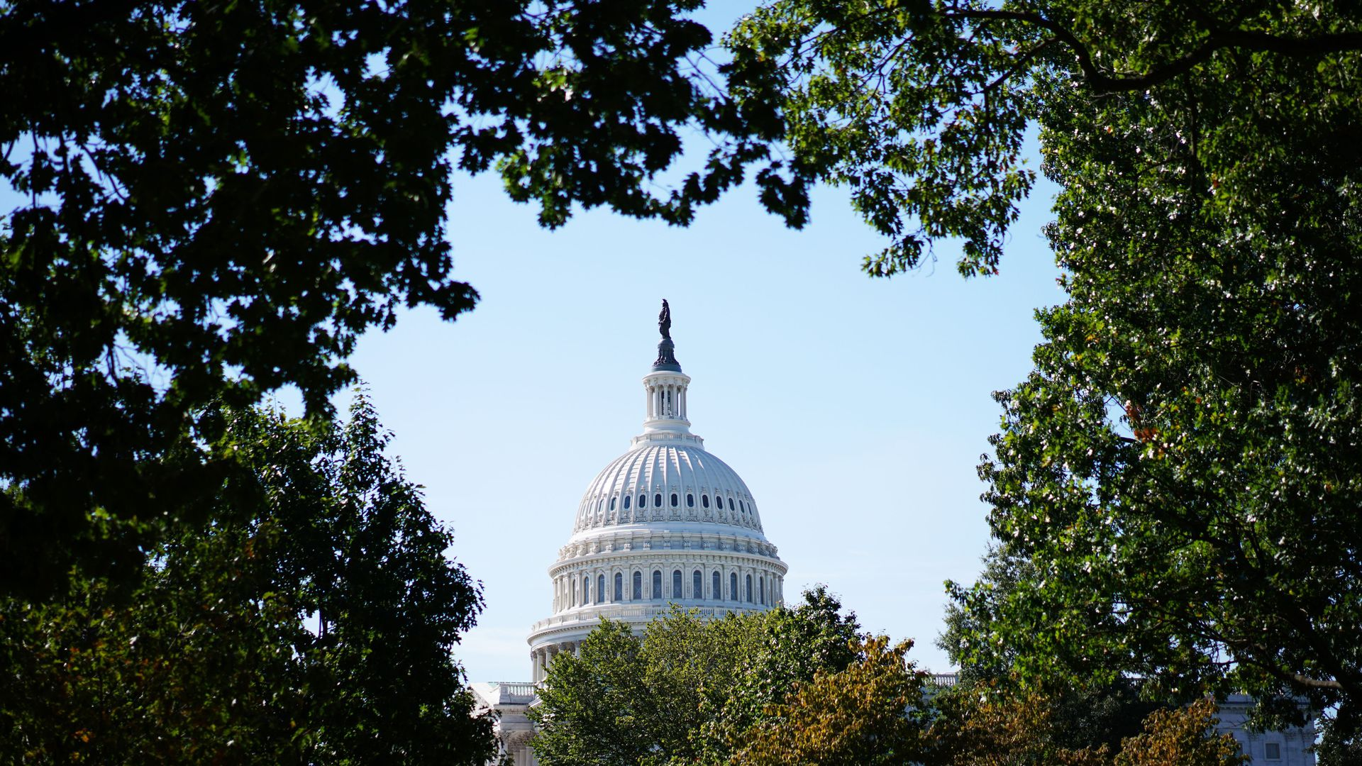 A long view of the U.S. Capitol Building surrounded by trees.
