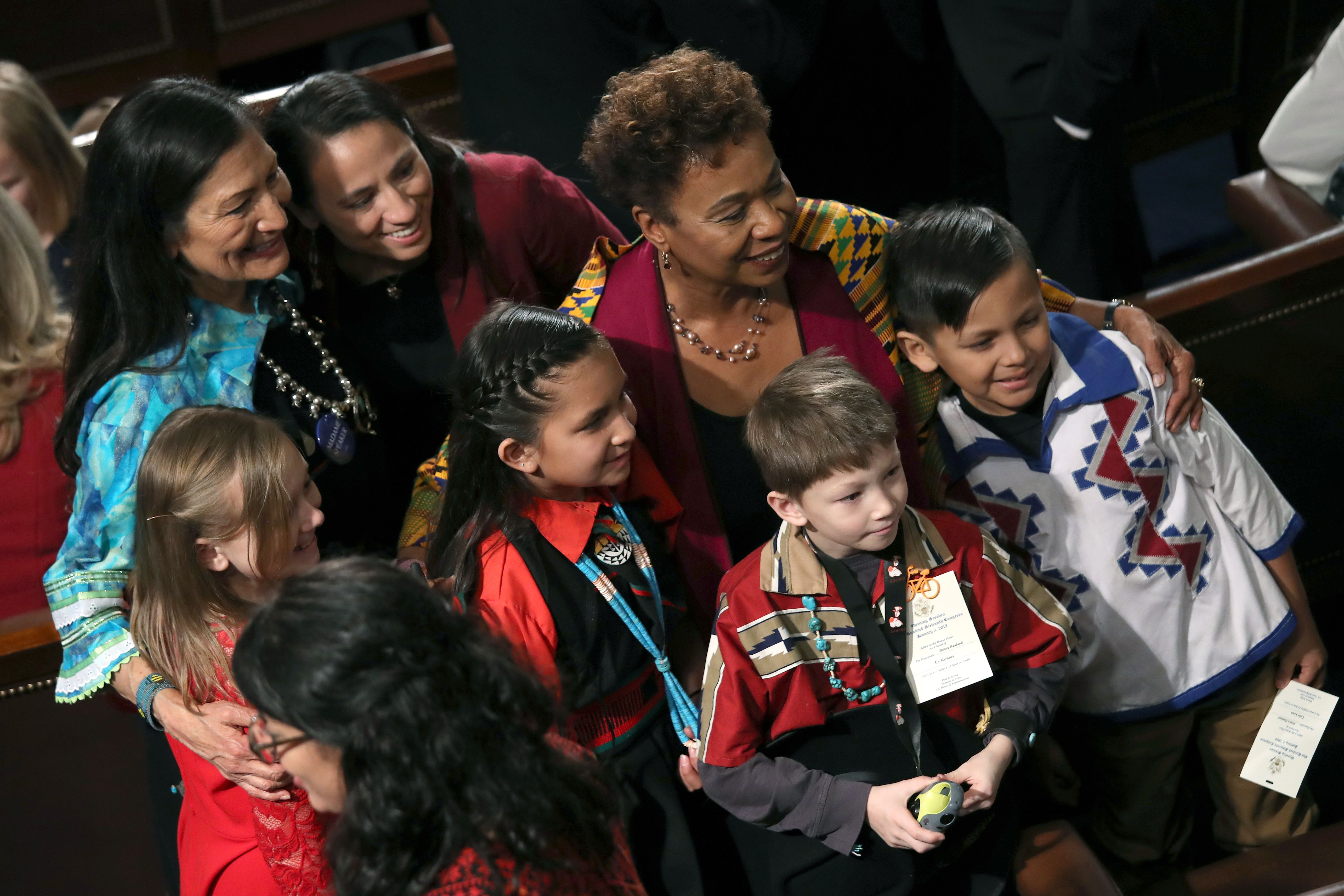 Deb Haaland, Barbara Lee, and children pose for a picture.