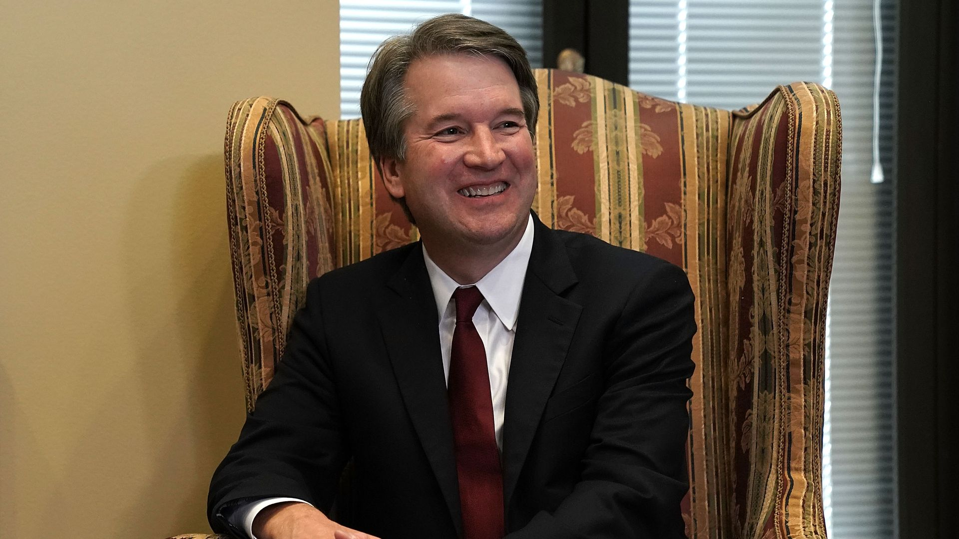 Brett Kavanaugh smiles wide while seated in an armchair