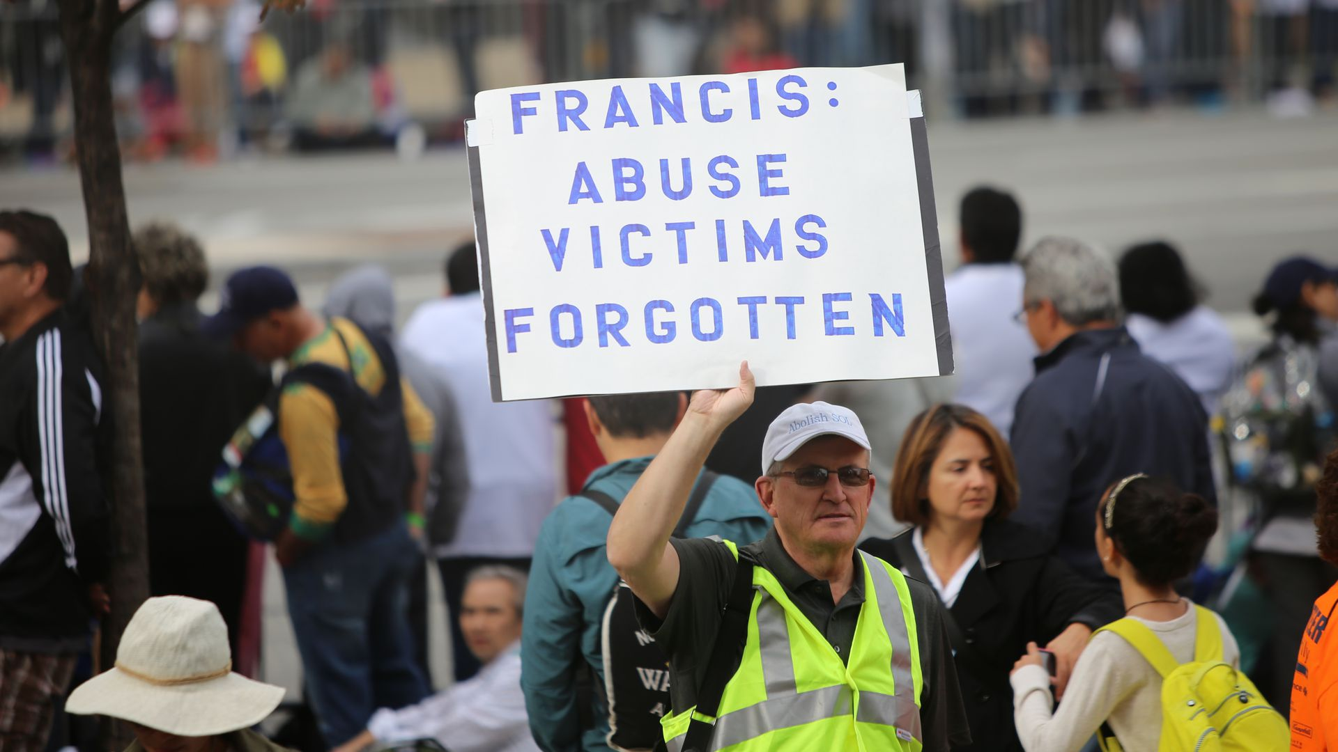 Man holding sign denouncing catholic church