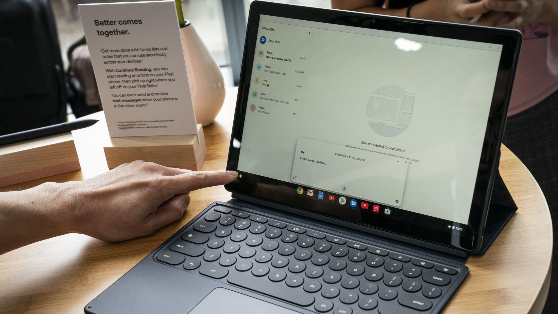 This image shows someone reaching for the keyboard of a Pixel Slate that's sitting on a table.