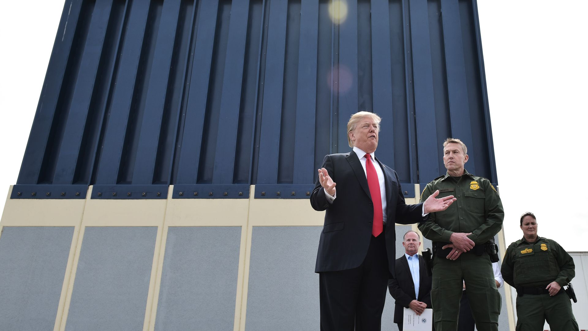 Trump stands in front of border wall prototype with law enforcement officers in green behind him