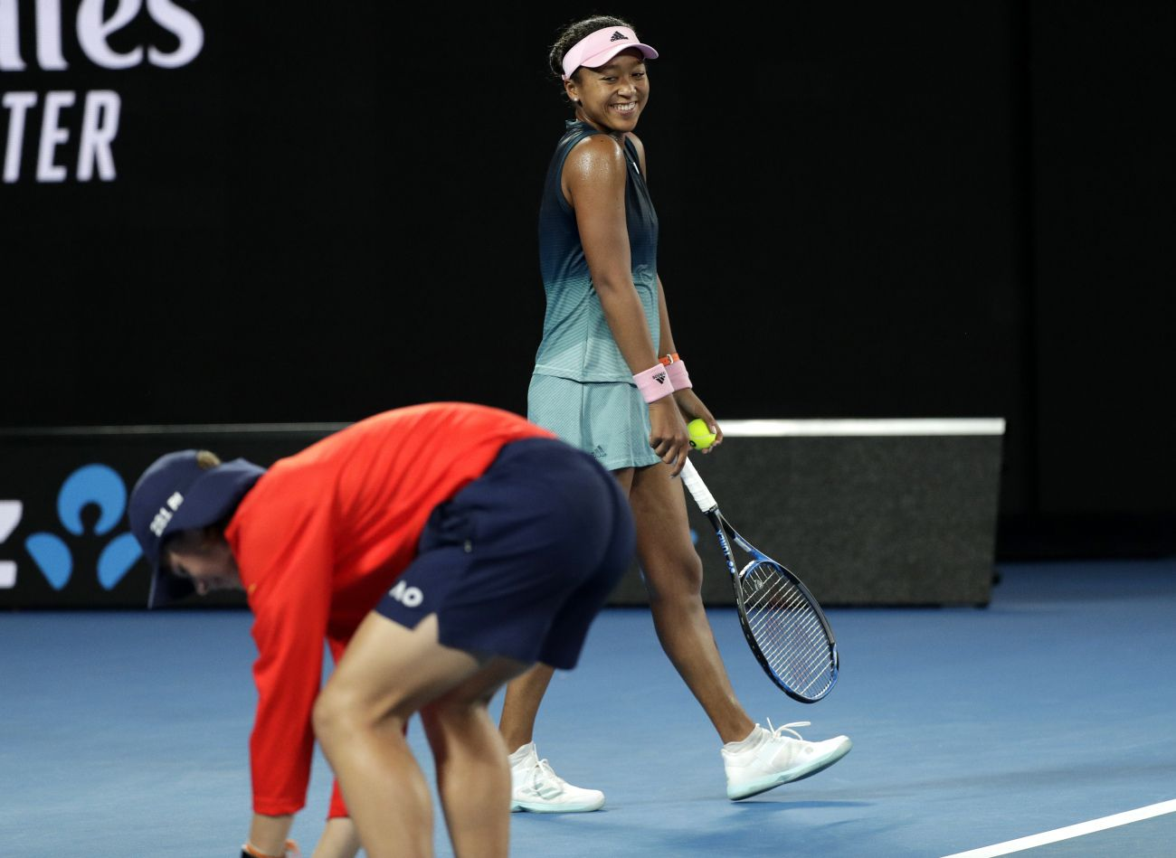 Japan's Naomi Osaka watches on as a ball kid attempts to catch a moth