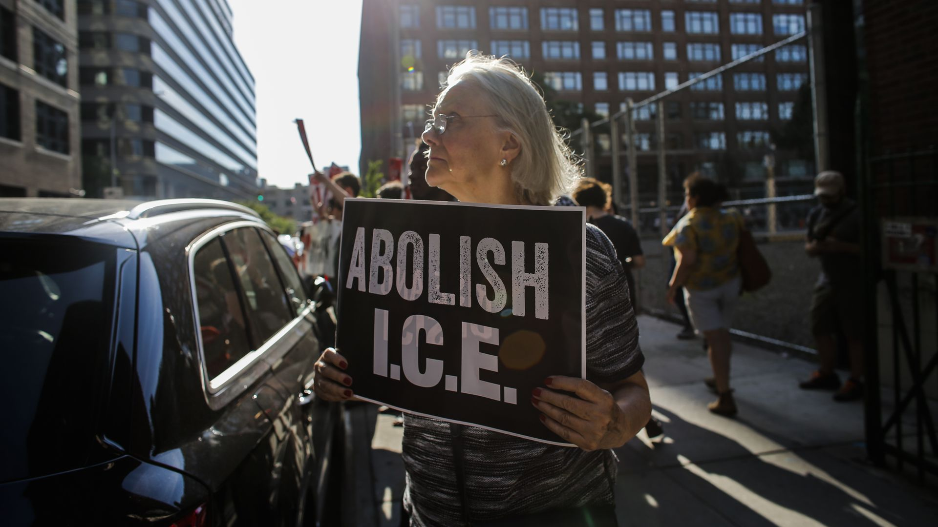 "A woman holds a sign in protest, reading ""Abolish I.C.E."""