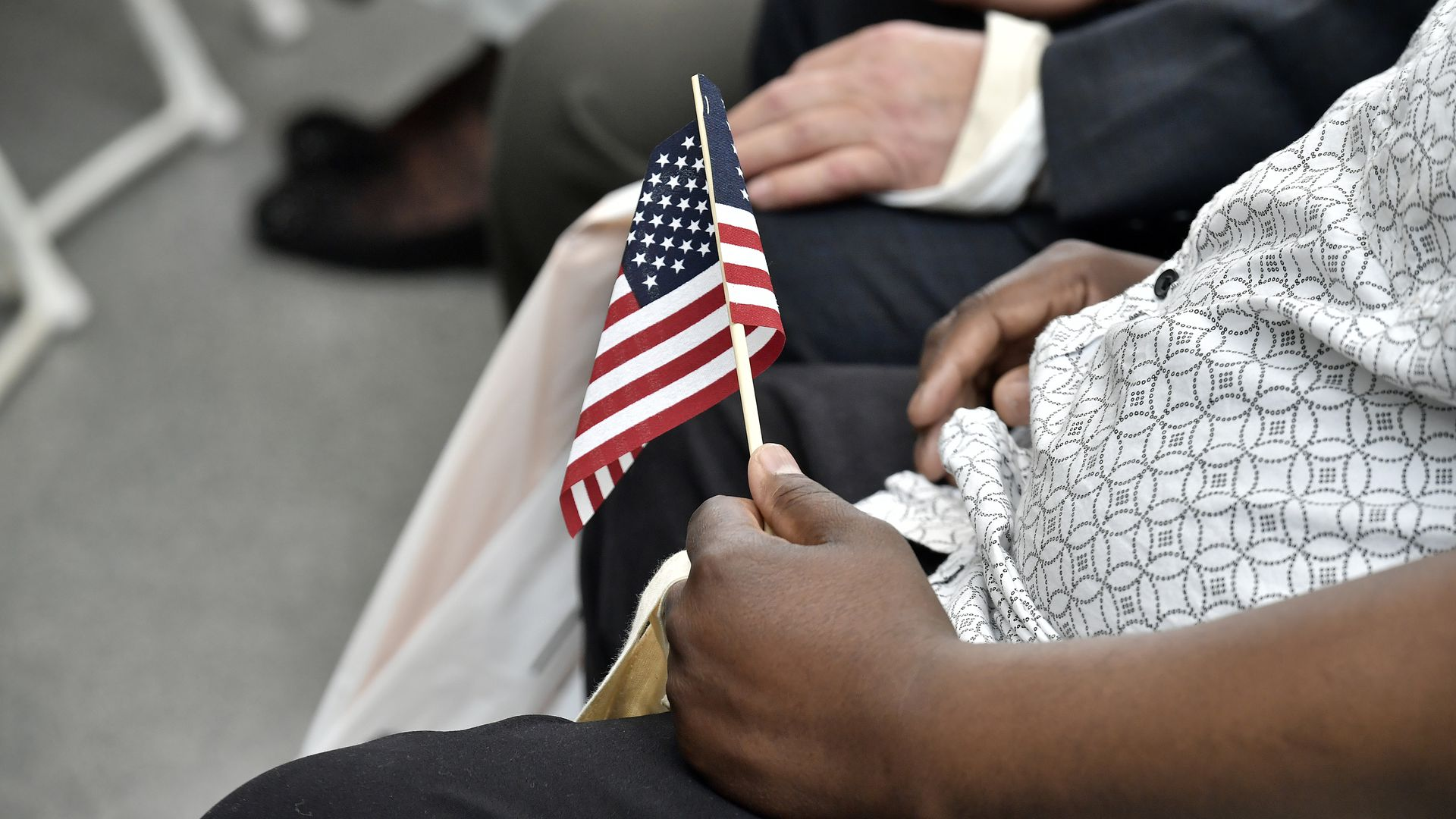 An attendee holds an American flag at a United States naturalization ceremony