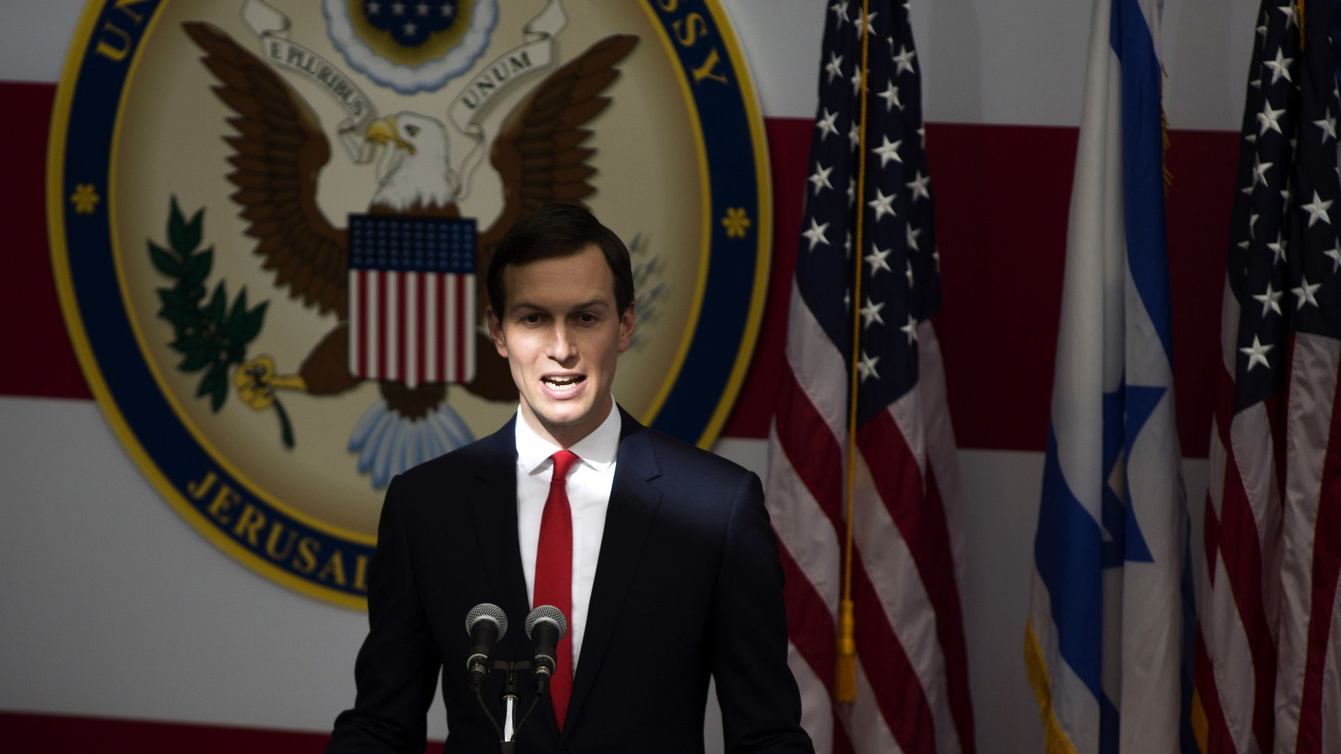Kushner stands behind a podium