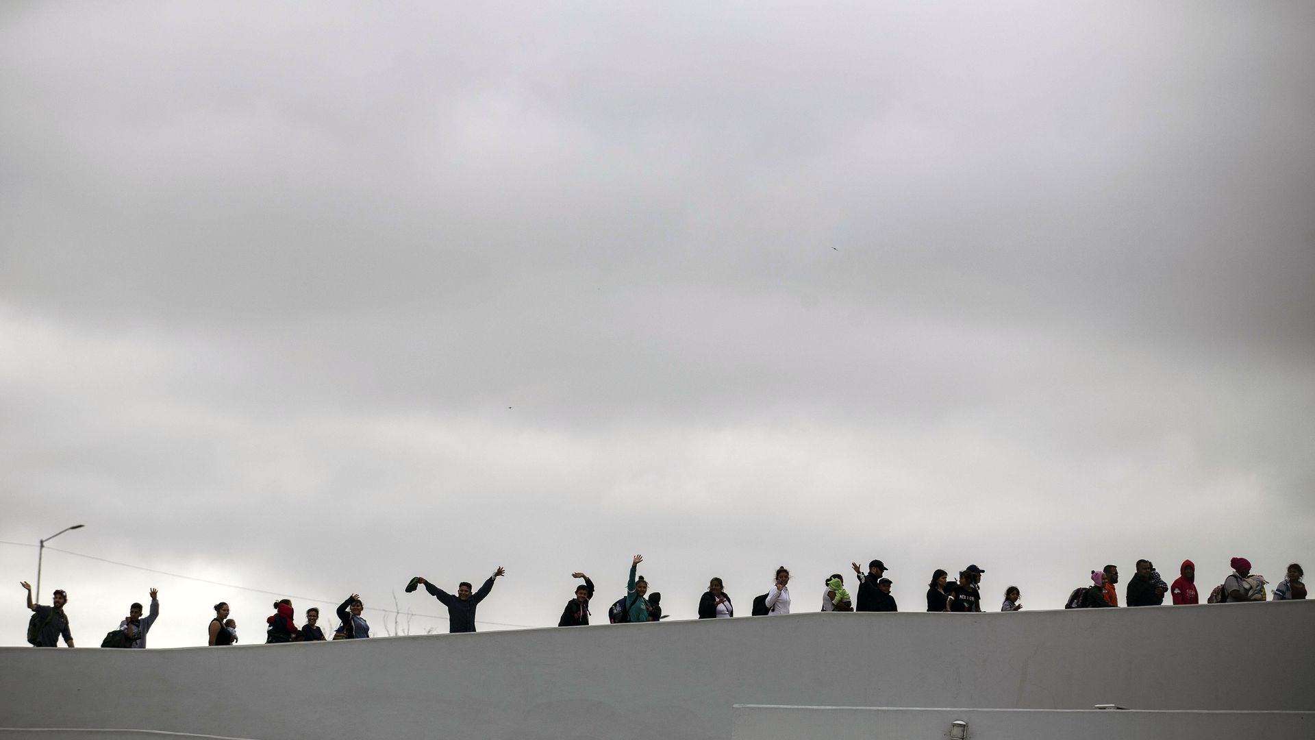 People waving overtop of a white wall with a grey sky in the background
