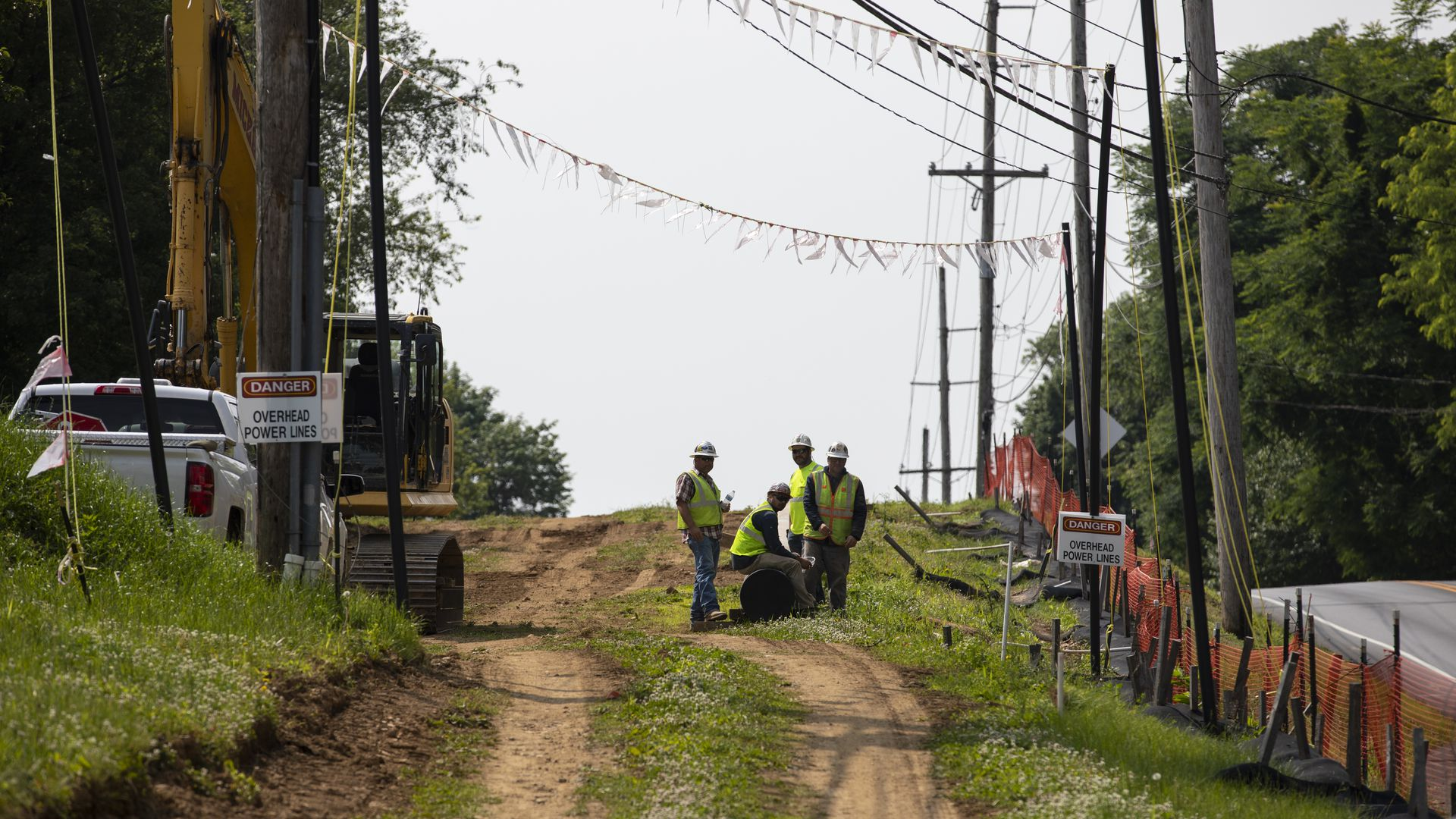 In this image, construction workers stand on a dirt road near a paved road.