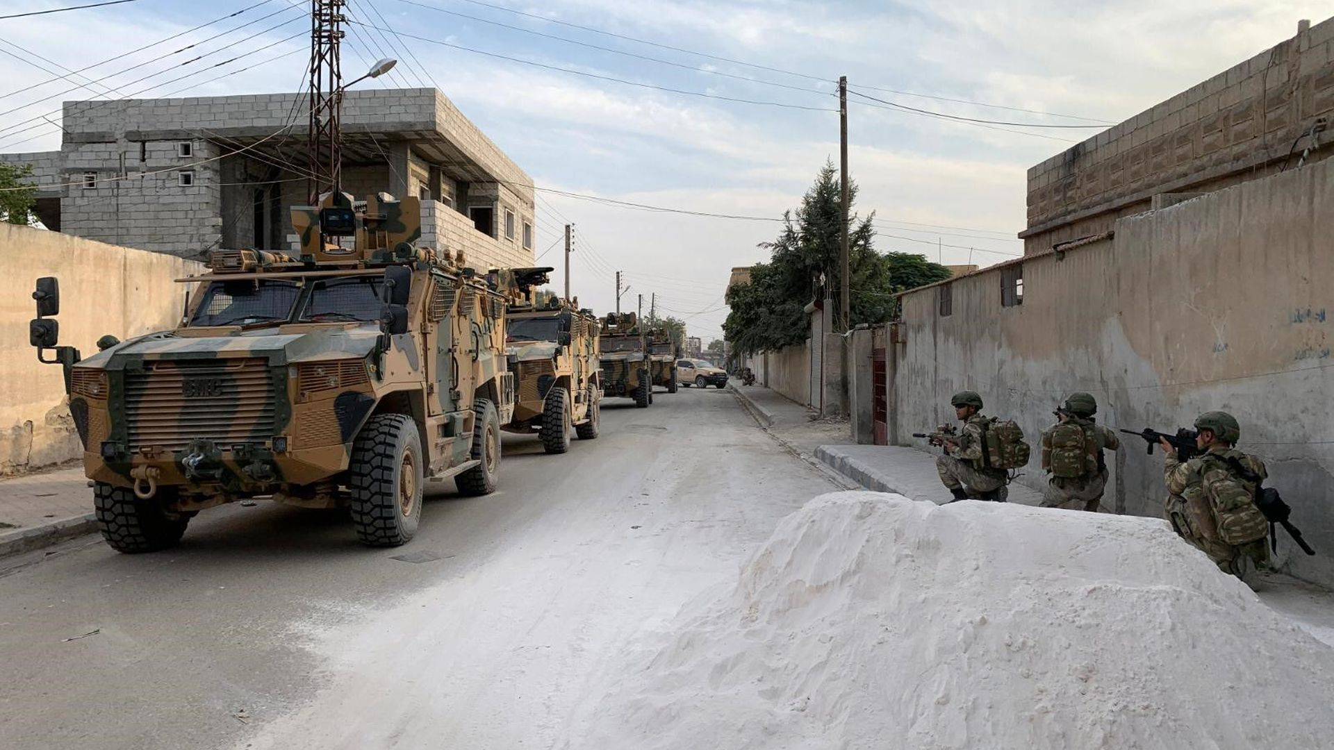 Turkish soldiers posted along a road in a Syrian border town