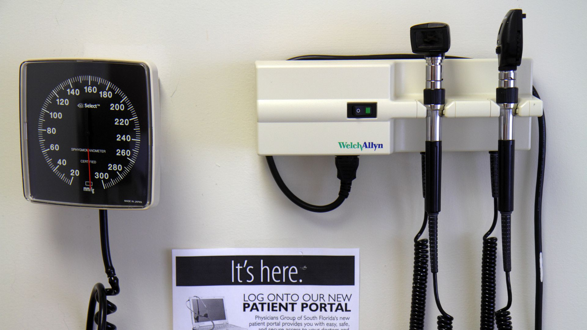 A blood pressure cuff, eye light, and ear tool hang on a wall in a doctor's office.