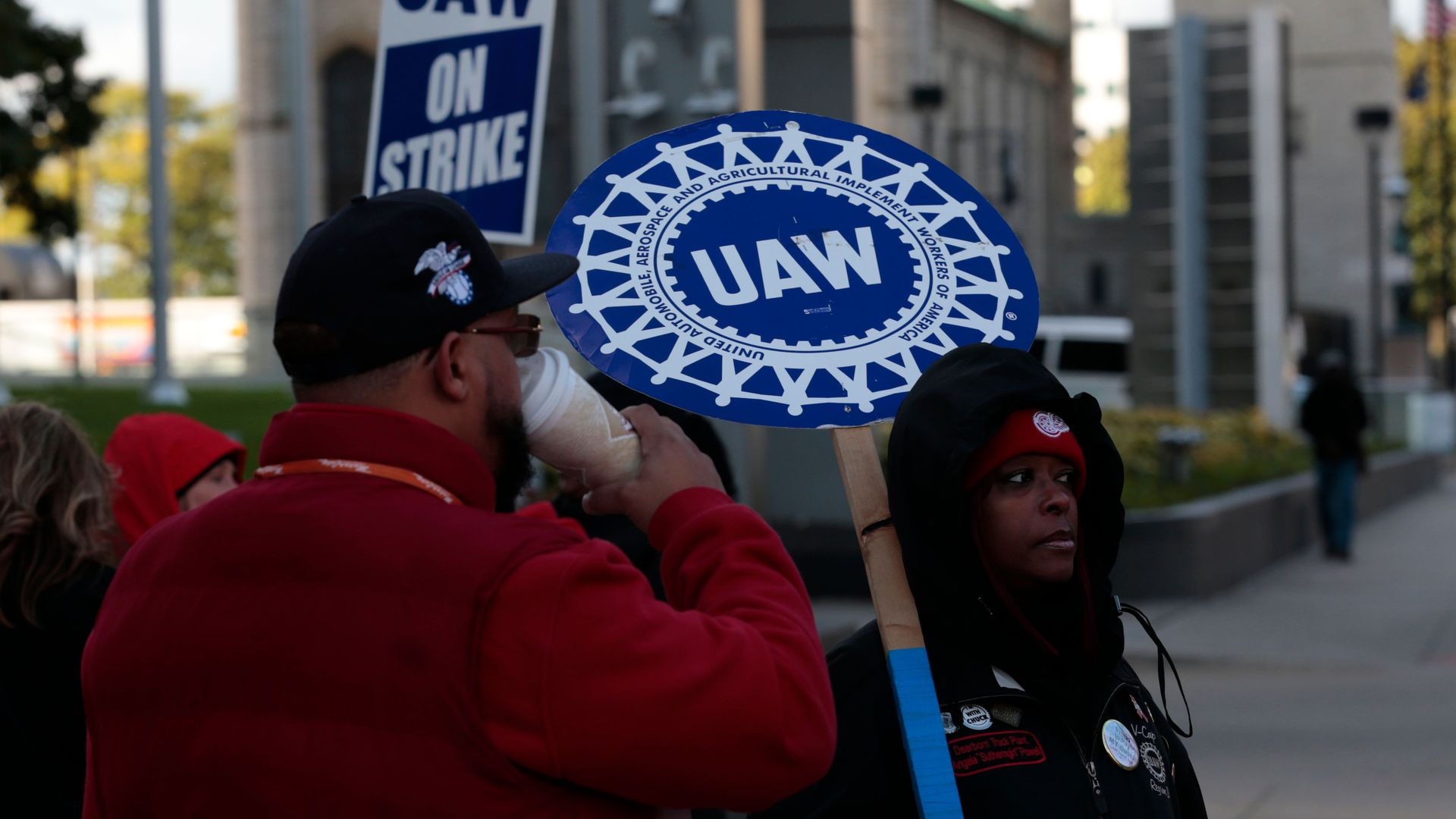 Members of the United Auto Workers picked outside of a building holding strike signs.