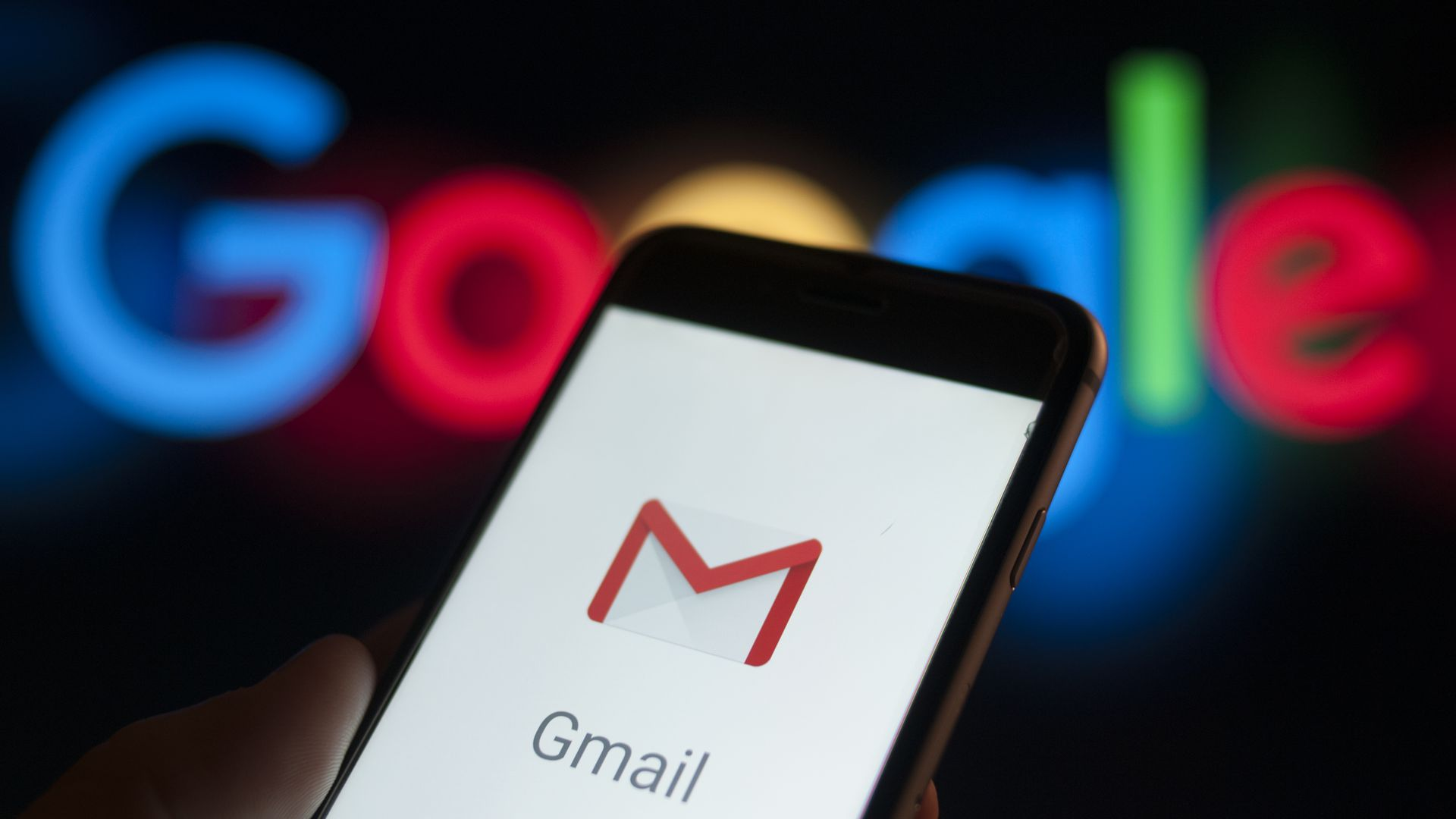 A phone screen with the Gmail app logo on it before the Google logo on a wall.
