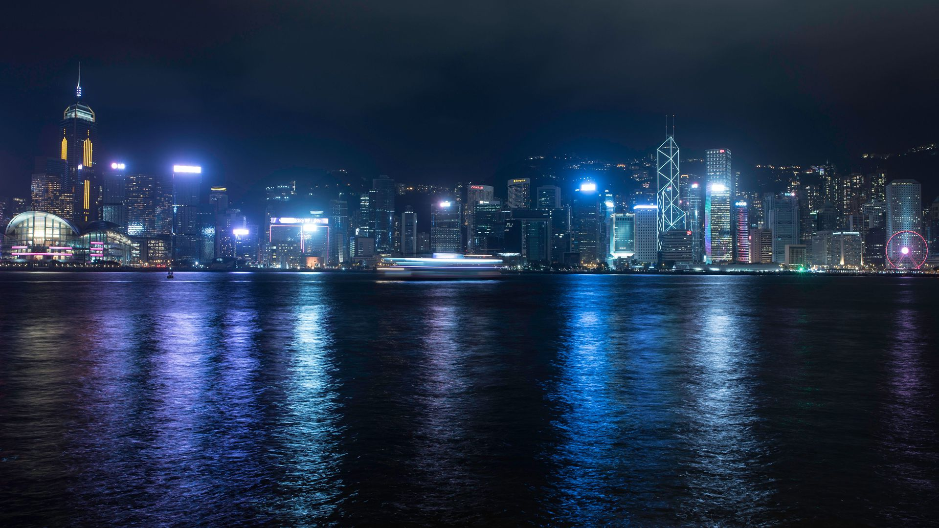 Hong Kong skyline in the dark with all the lights on. Everything has a neon blue hue in the darkness.