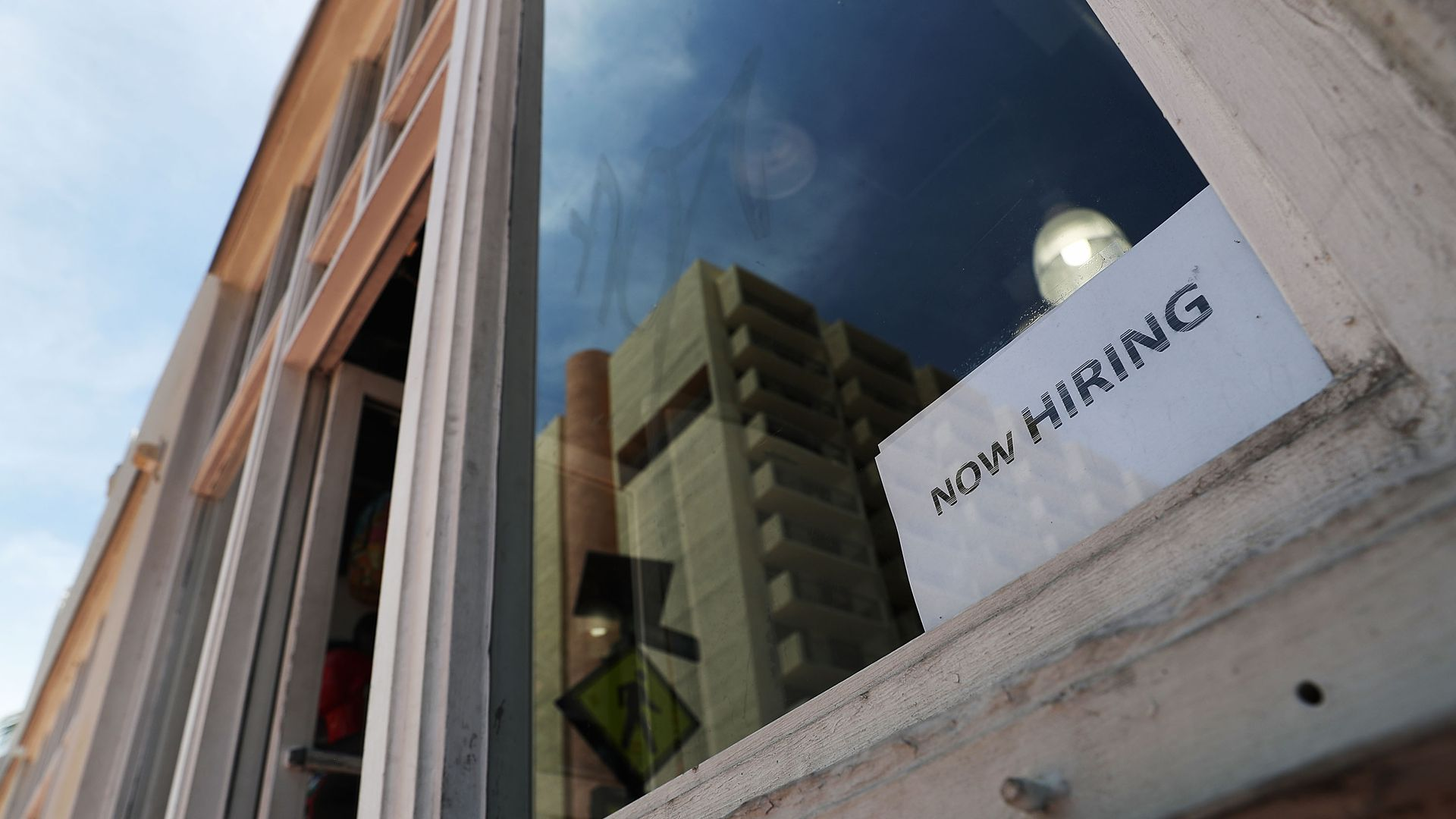 "A simple ""now hiring"" sign in the window of a shop"