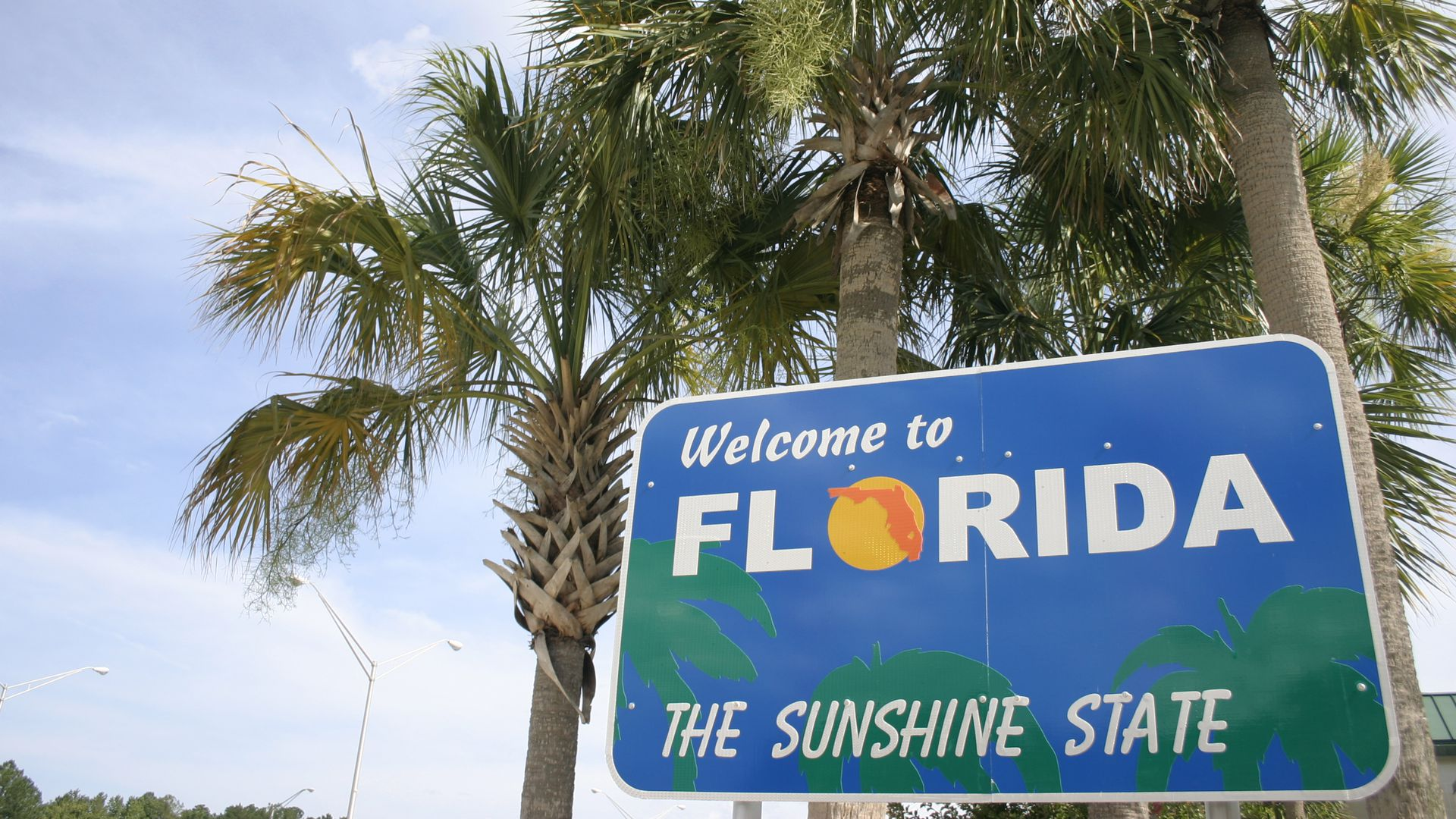 Welcome to Florida sign in front of palm trees