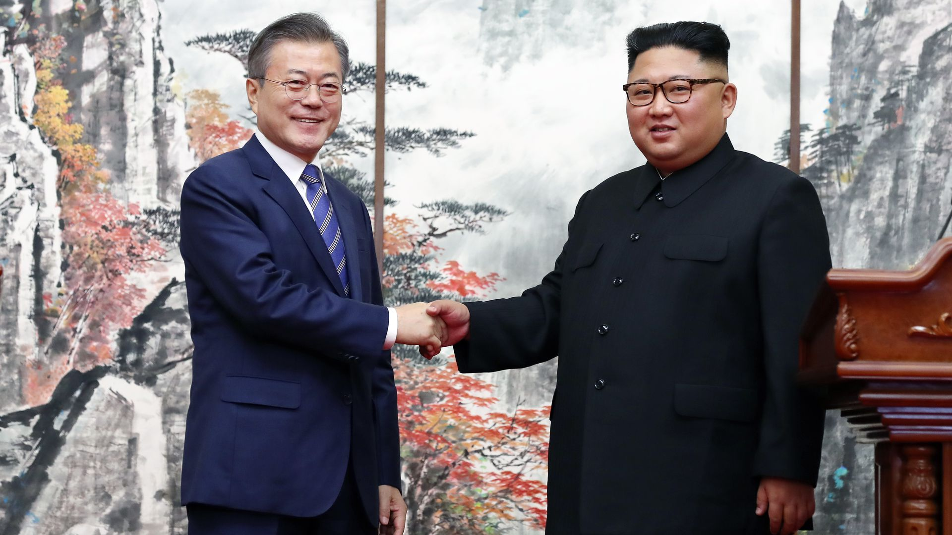 Moon Jae-in and Kim Jong-un shake hands.