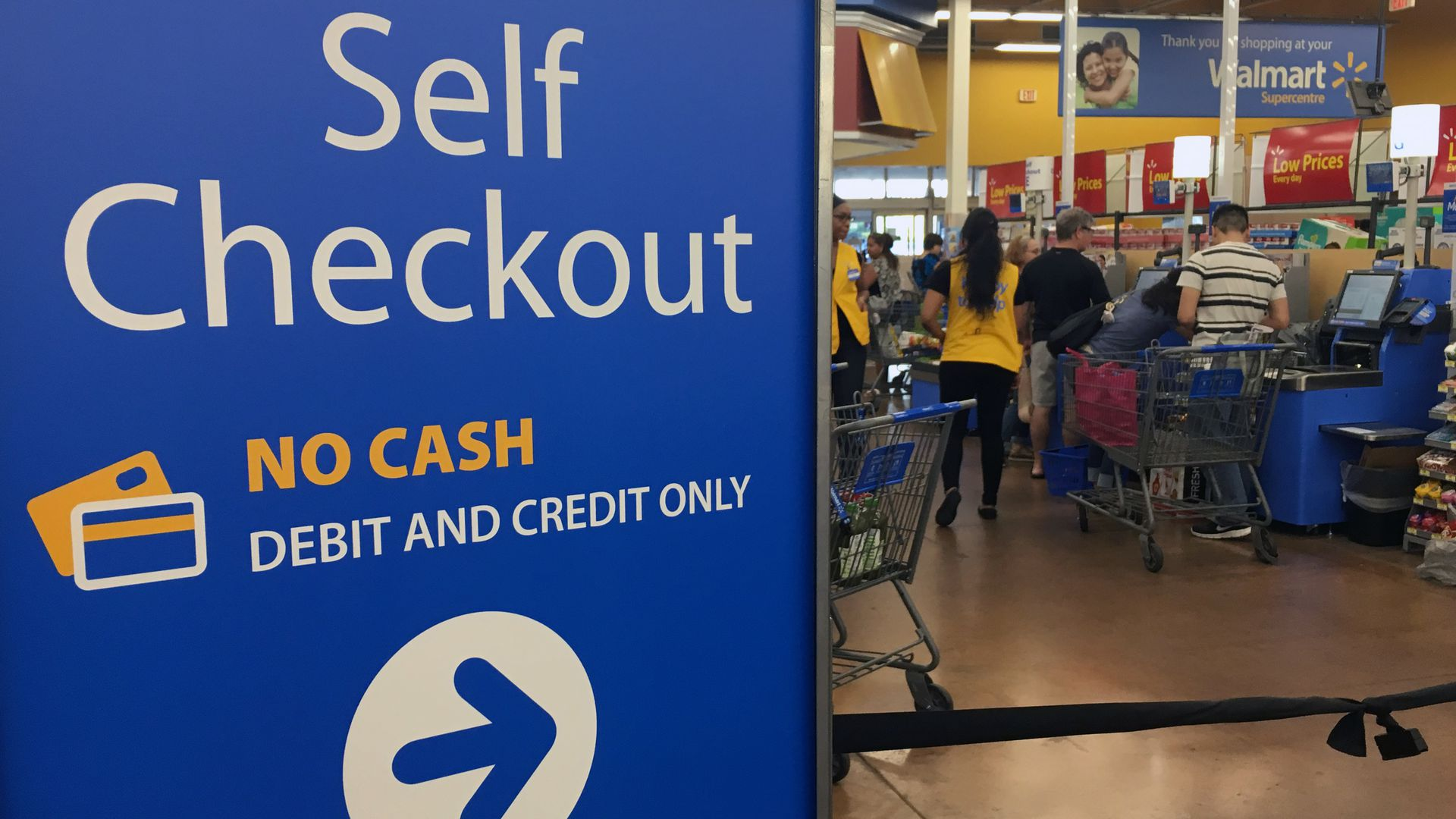 A Walmart sign pointing toward self checkout
