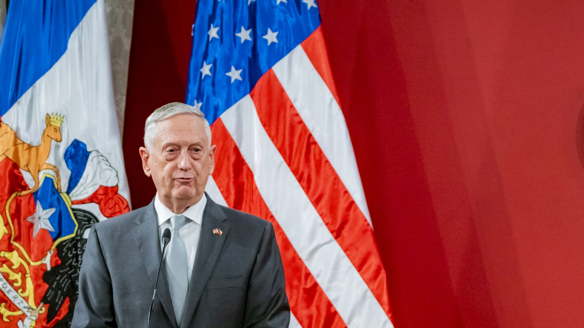 Jim Mattis purses his lips standing before a red background and two flags