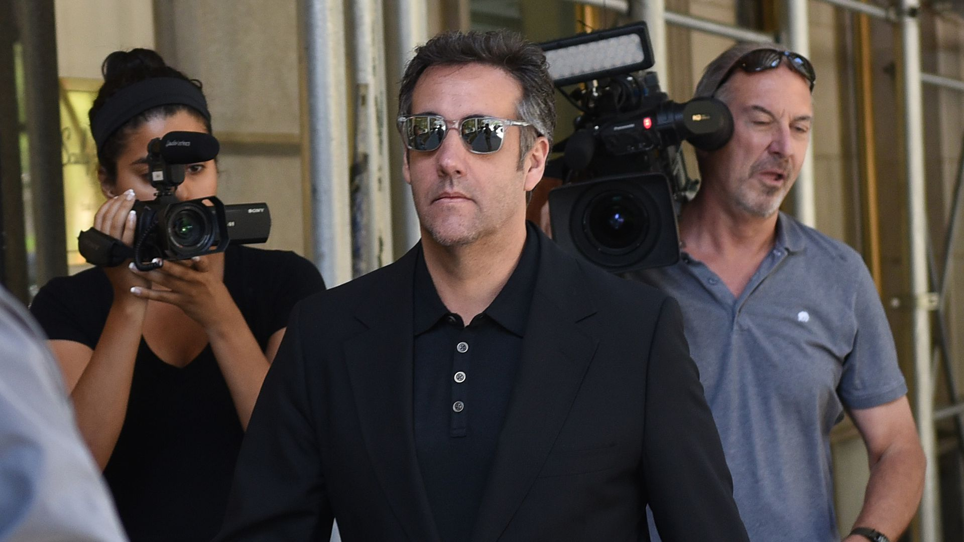 Michael Cohen walks down a sidewalk in sunglasses