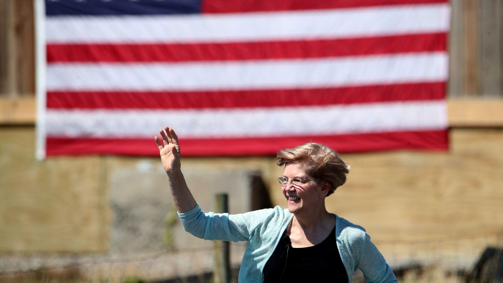 Elizabeth Warren waves in front of an American flag.
