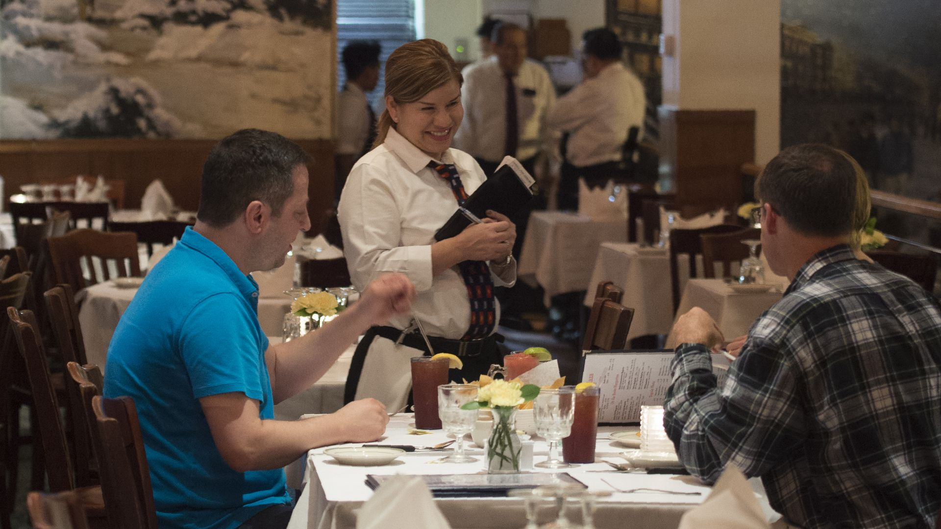 A waitress takes takes orders at the Salvadorian and Latin American restaurant in Washington, DC.