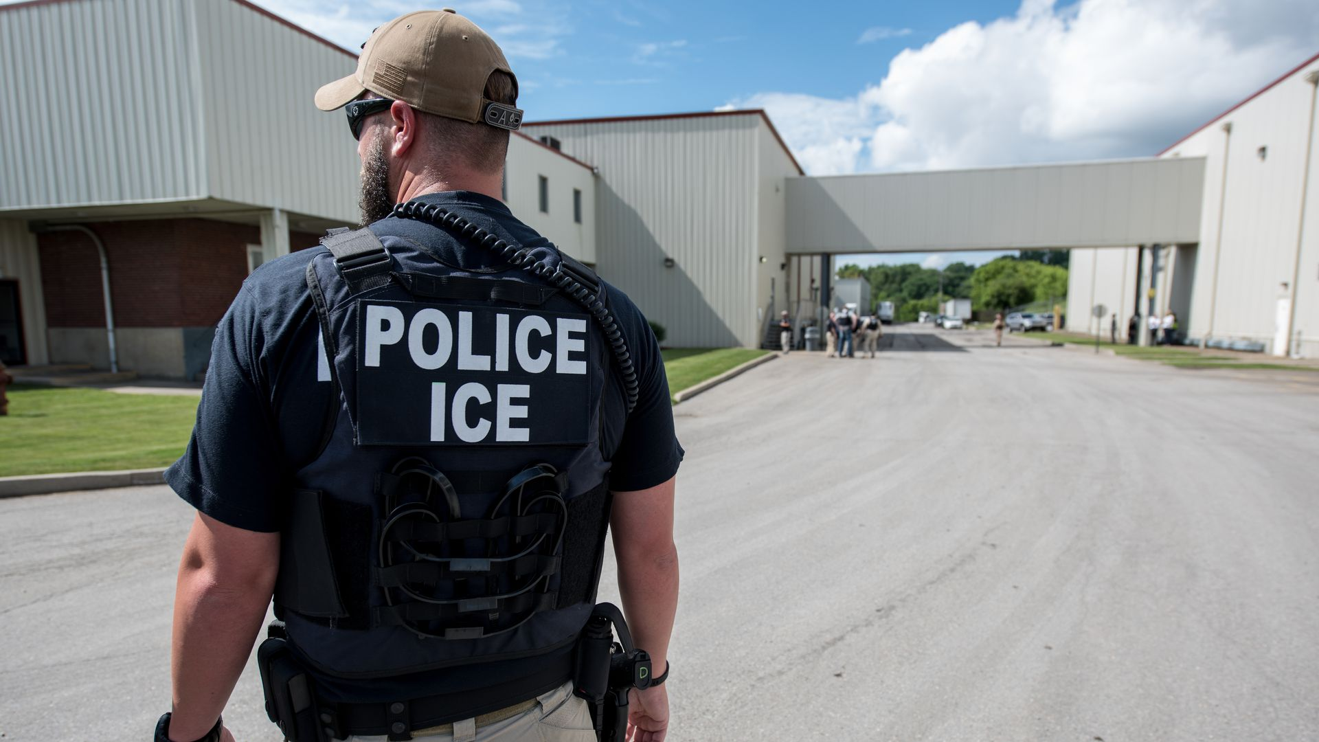 """A white man with a hat and a vest that says """"Police ICE"""" on it with his back to the camera."""