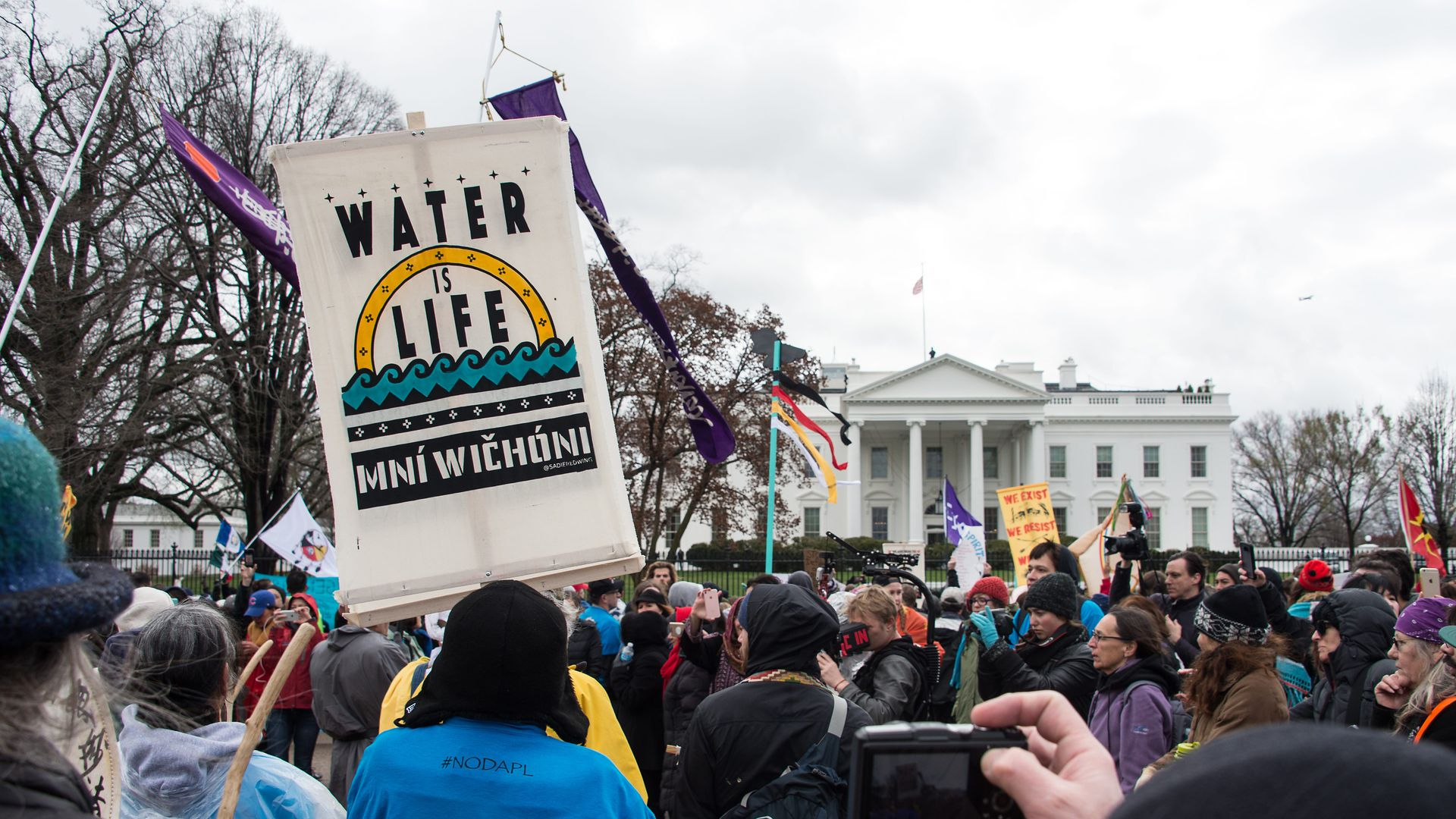 """In this image, protestors hold a banner that reads """"water is life"""" in front of the White House."""
