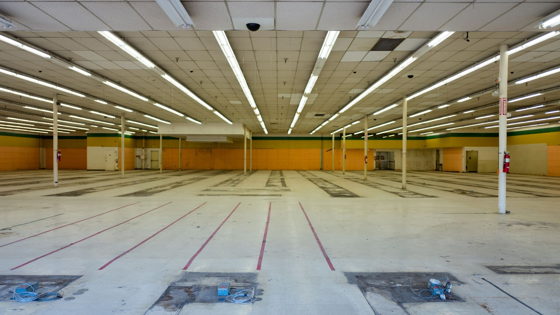 This image shows the inside of an empty and abandoned retail store with the fluorescent lights on.