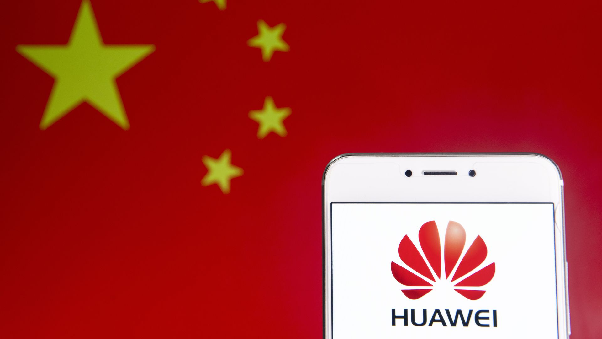 Huawei logo on a phone screen in front of the Chinese flag