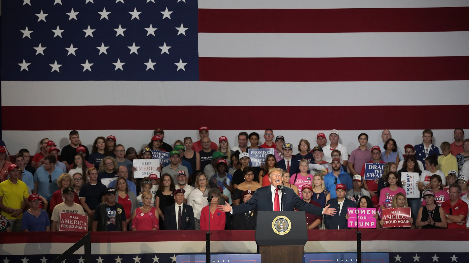 President Trump speaking in front of a crowd and an American flag backdrop at a rally.