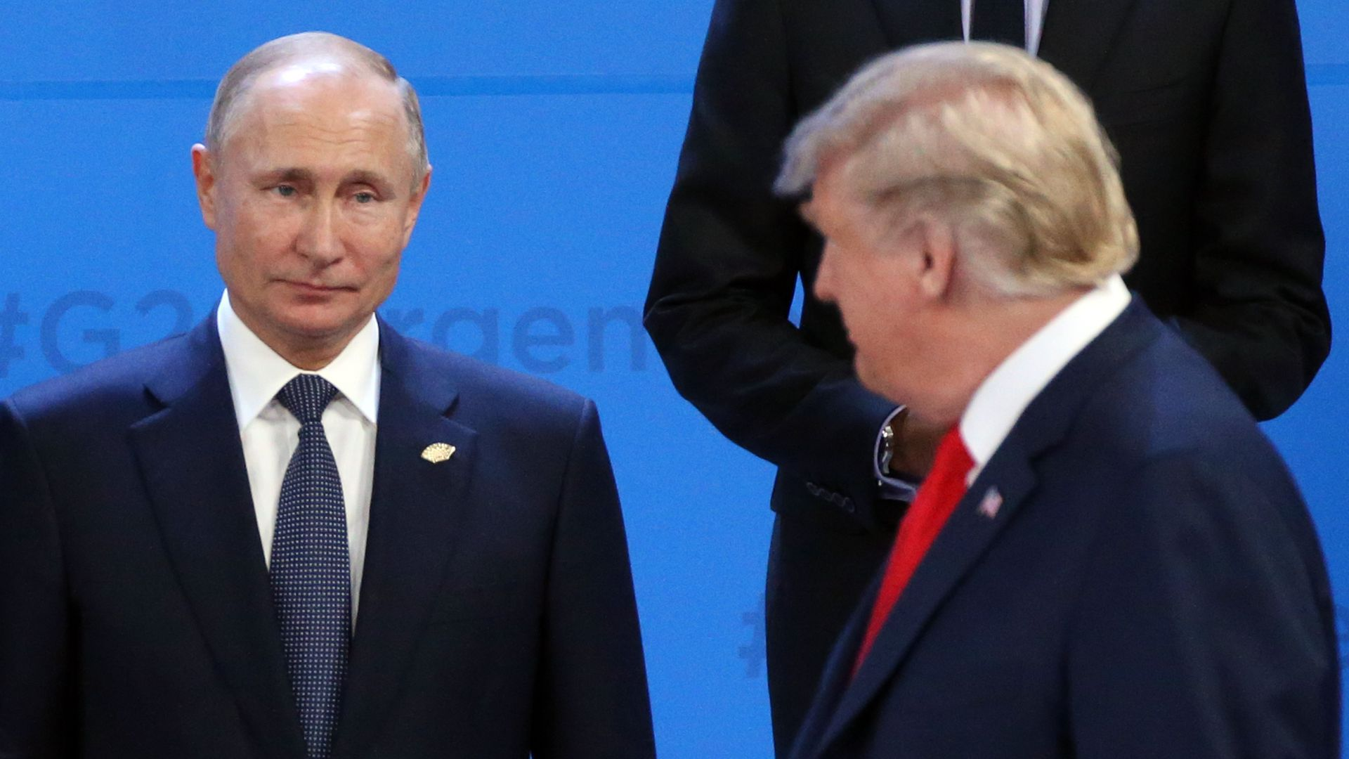 Putin on the left looks at Trump