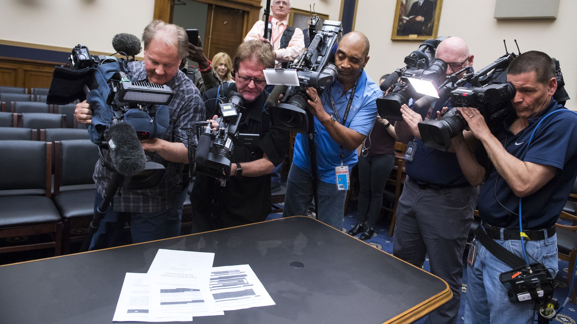 In this image, a crowd of reporters with cameras take pictures of papers in the Mueller report as it sits on a table.