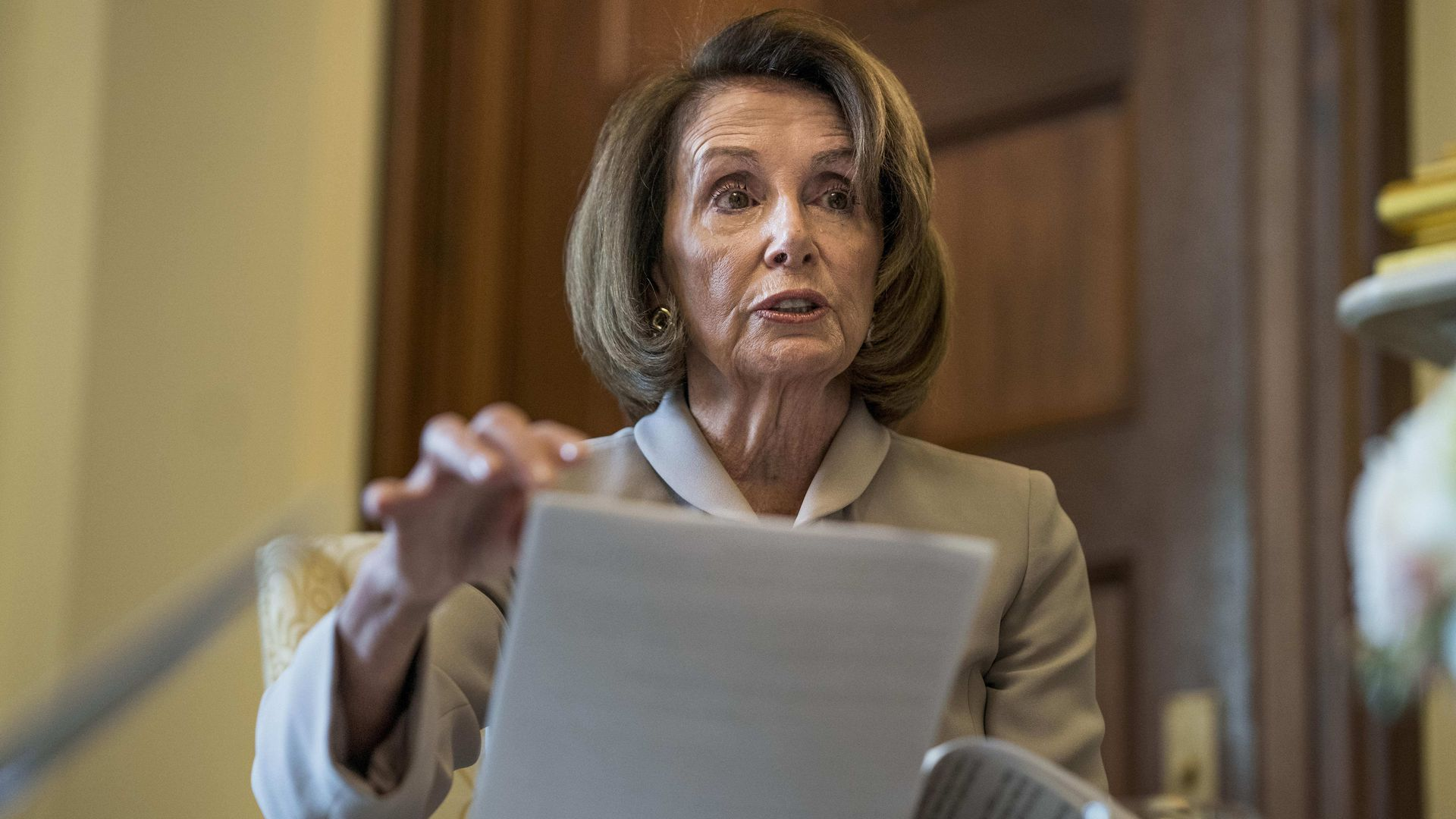 Nancy Pelosi holding a few sheets of paper while sitting