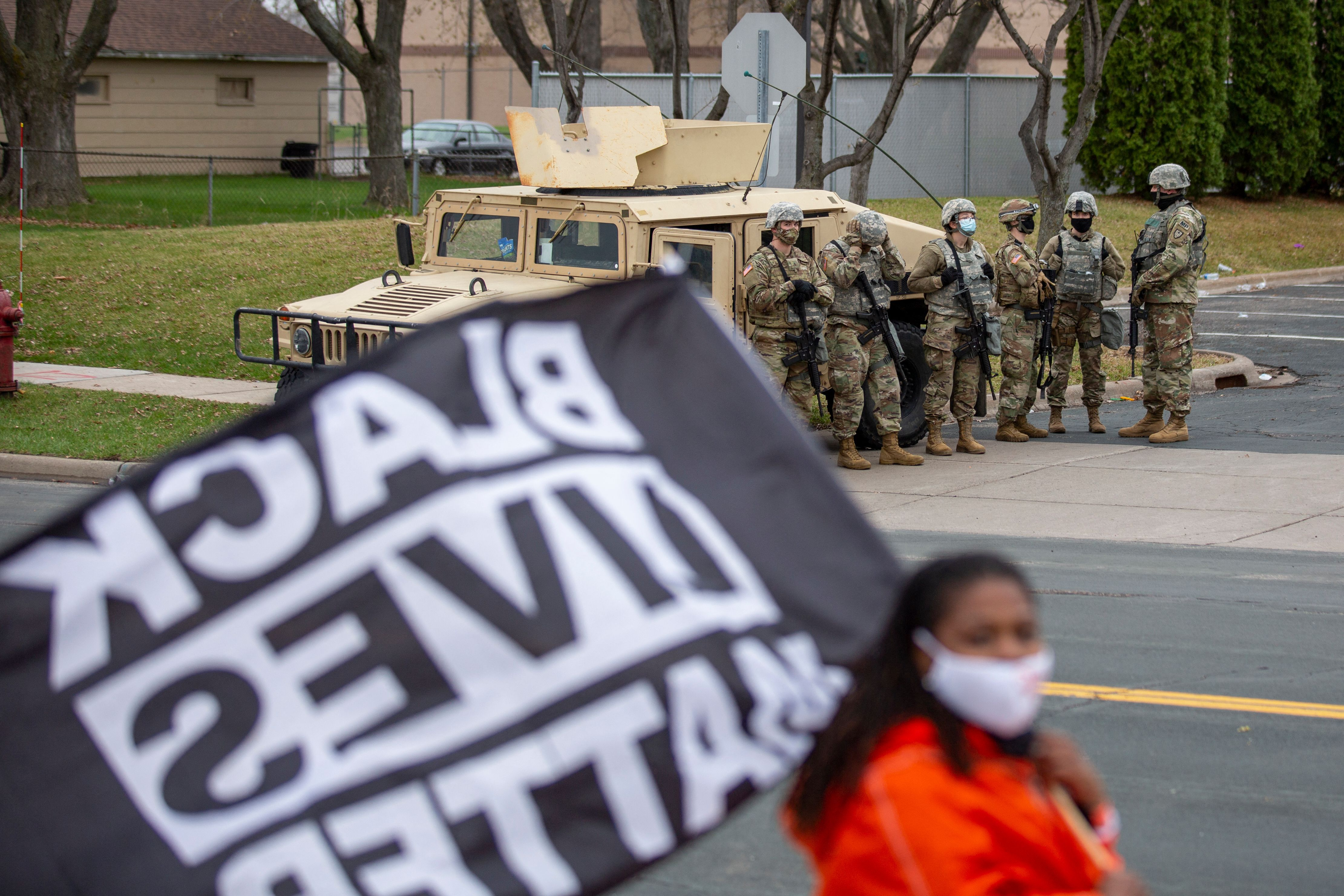 Minnesota National Guard and law enforcement members stand guard outside the Brooklyn Center Police Station