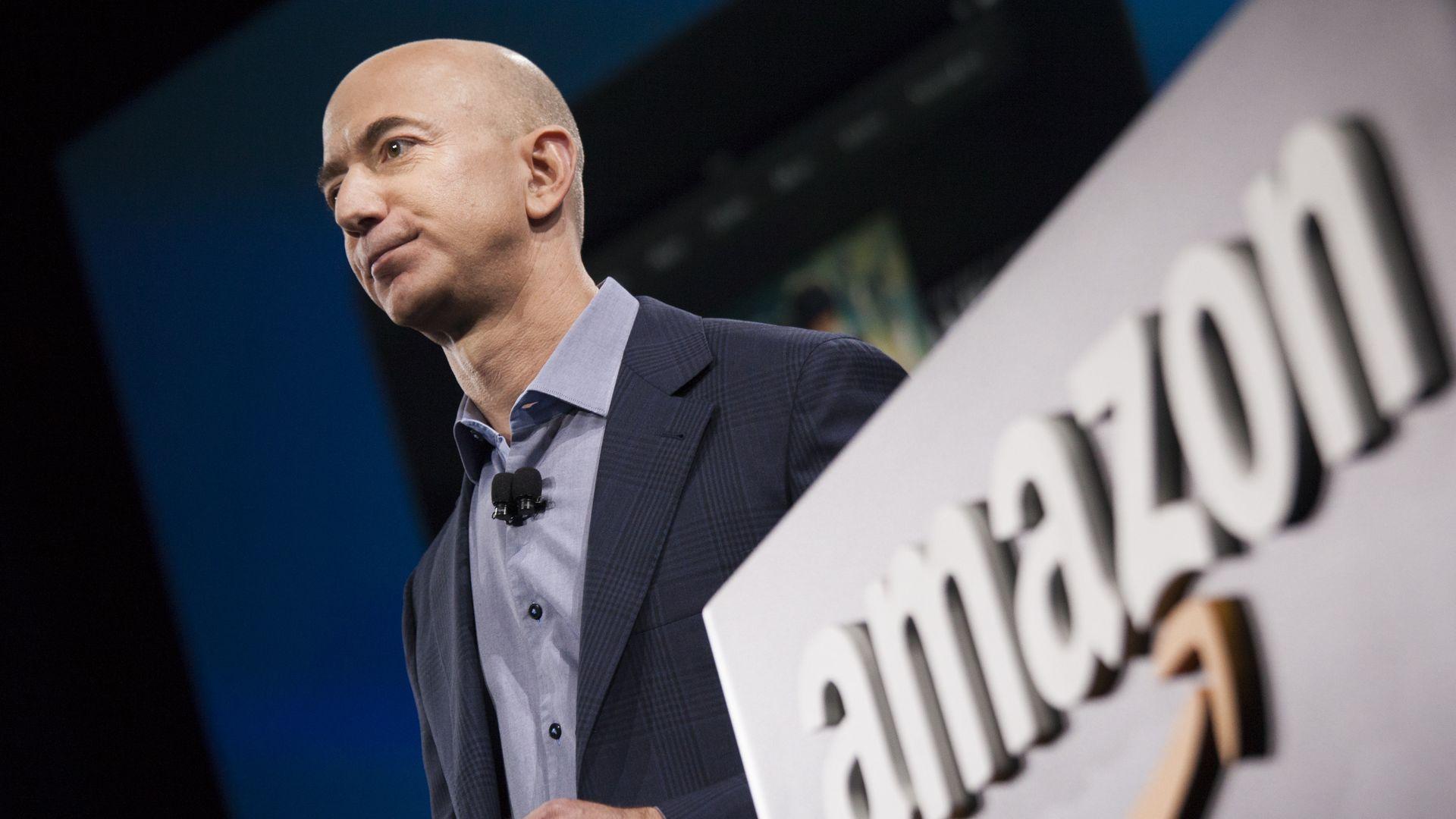 Jeff Bezos in front of an Amazon logo