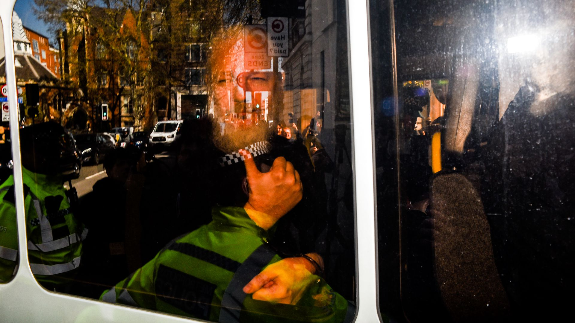 In this image, Assange gives a thumbs up to reporters from inside a vehicle.