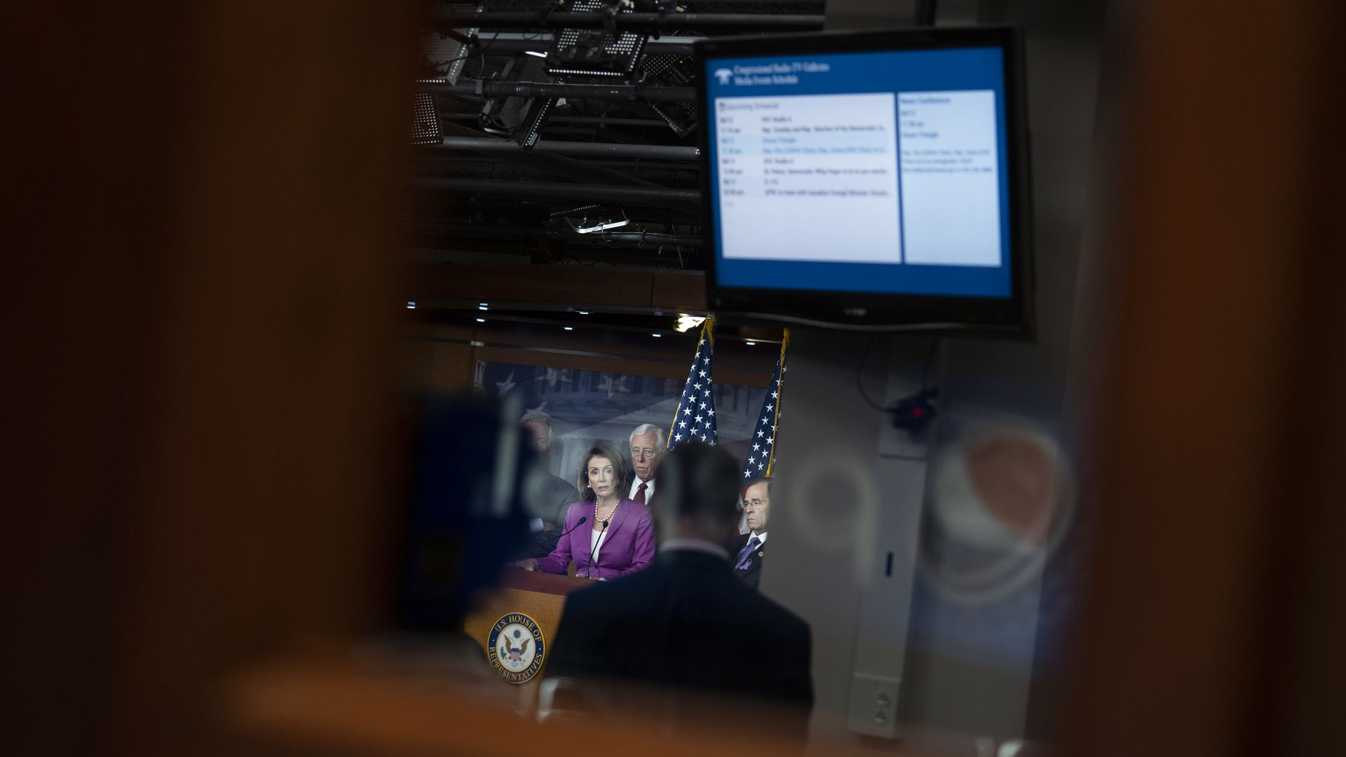 In this image, Democratic leaders stand on stage in the background of a blurred camera shot. They are standing underneath a presentation screen.