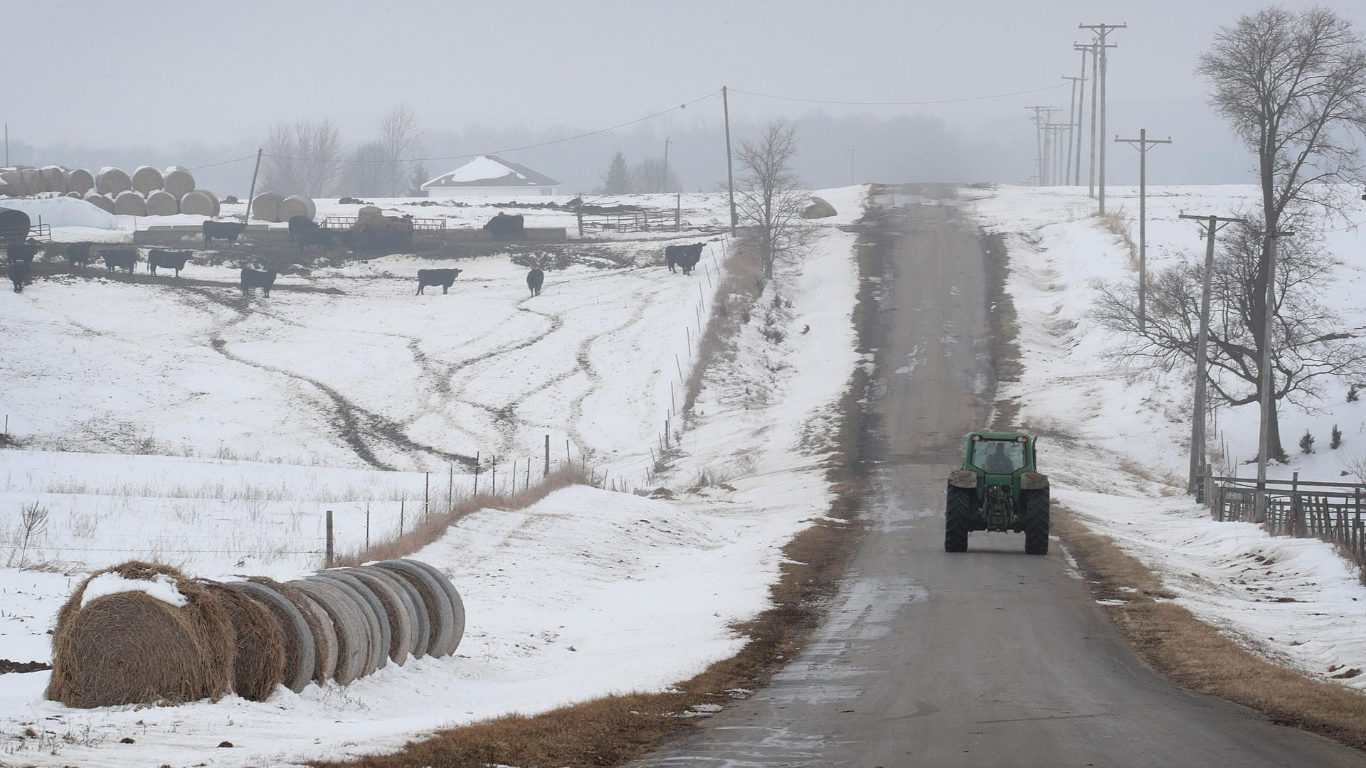 In this image, a tractor drives away from the camera on a snowy one-lane road.