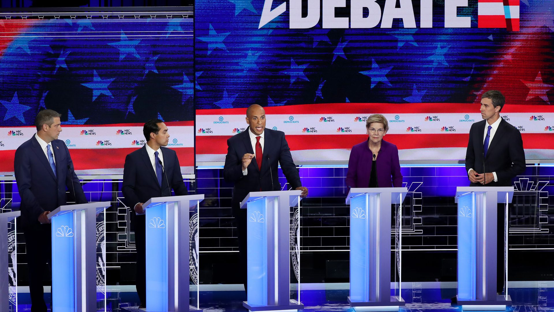 The debate stage with candidates at their podiums.