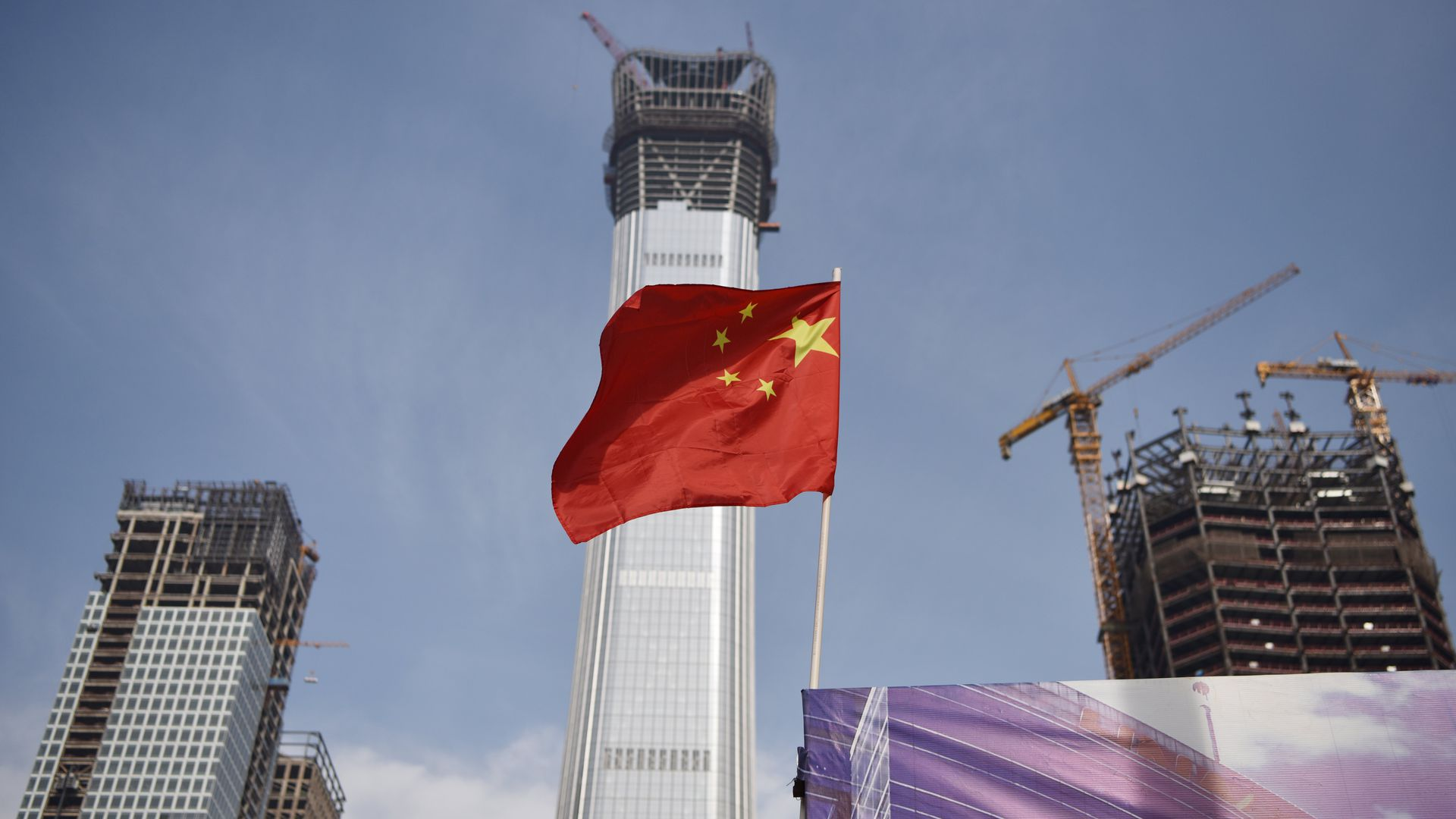 A Chinese national flag flies at the construction site for new buildings in Beijing's central business district