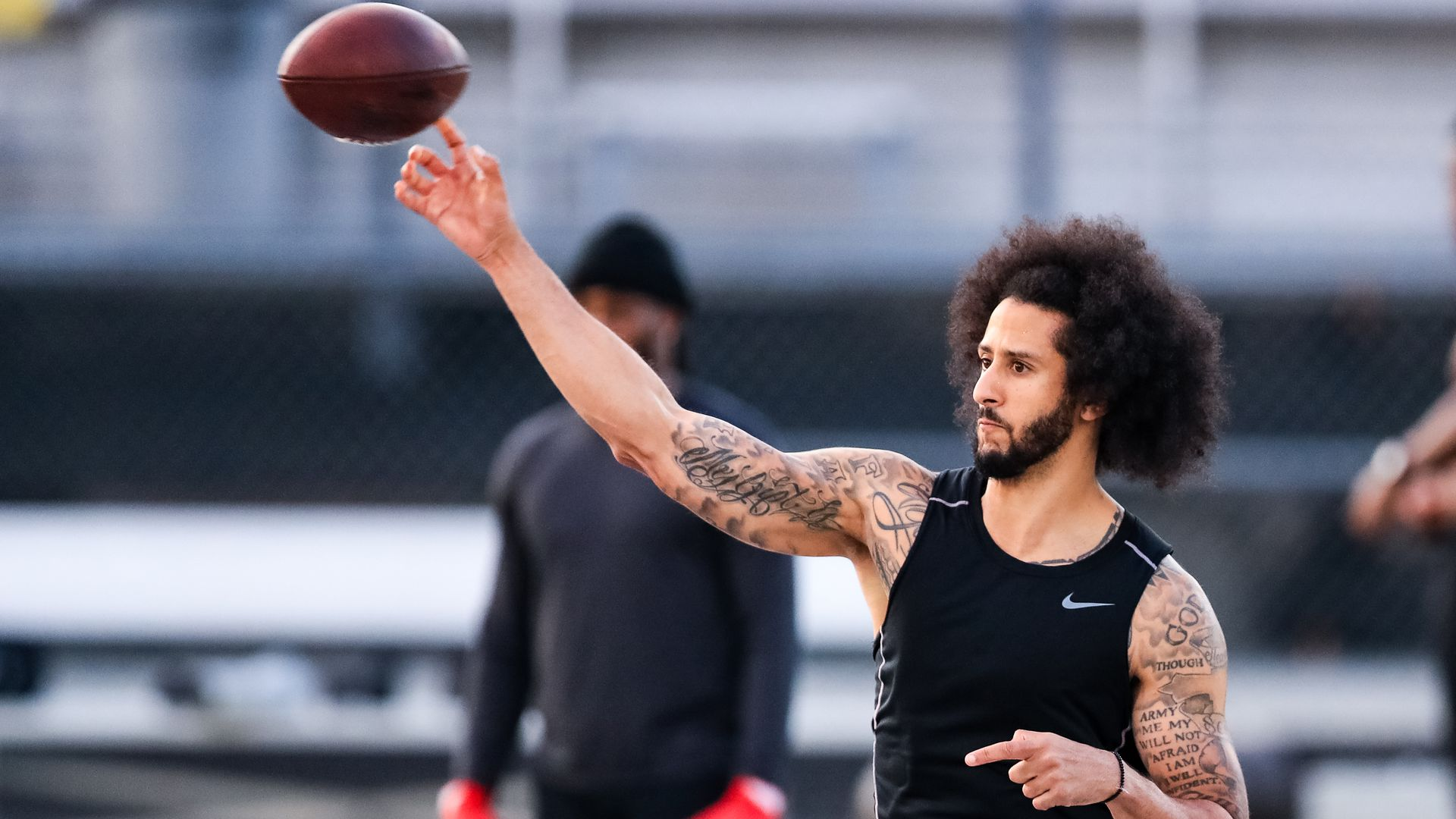 In this image, Colin Kaepernick tosses a football on a football field