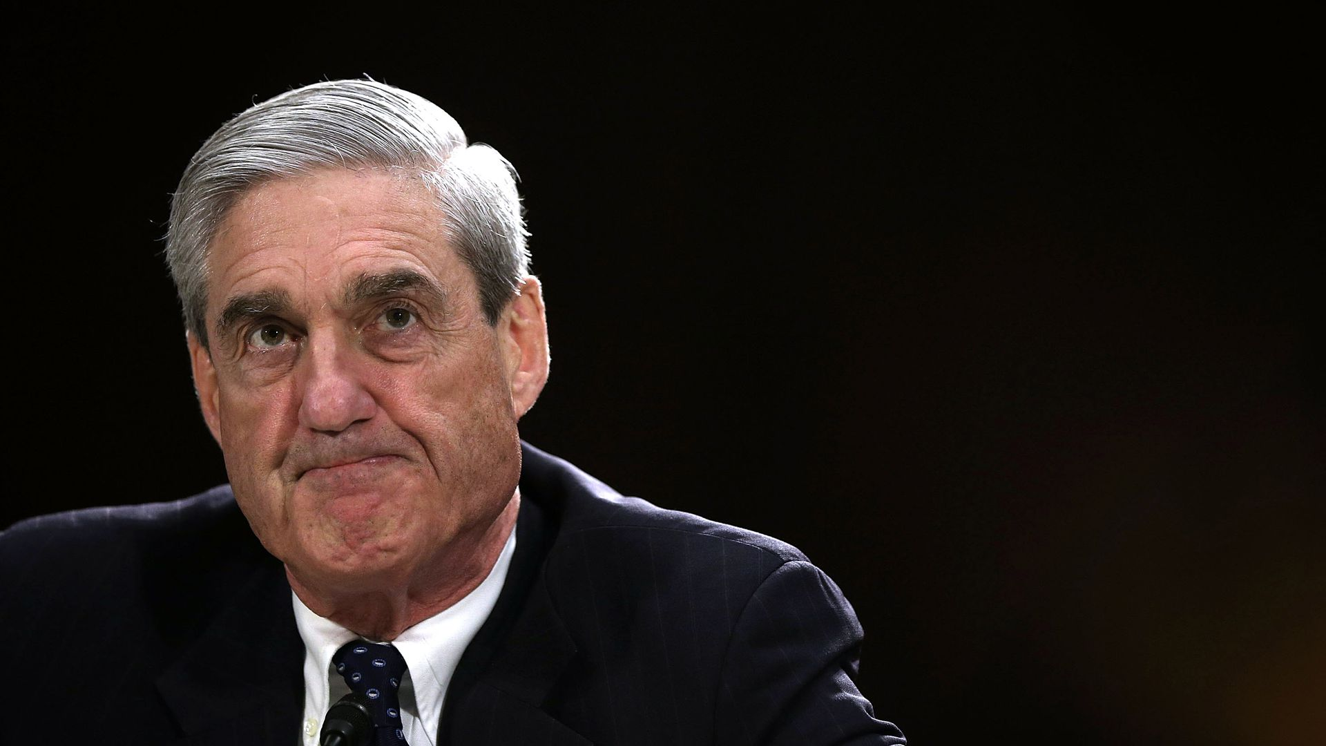 Bob Mueller before a black background grimaces.