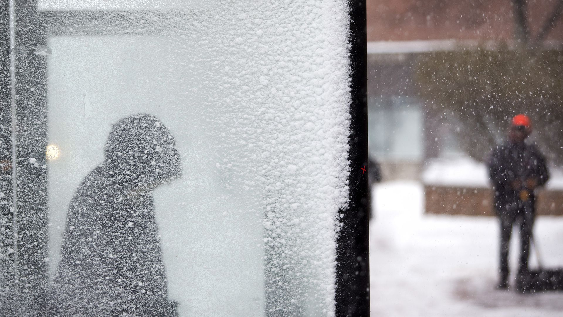 woman in a snowy bus stop