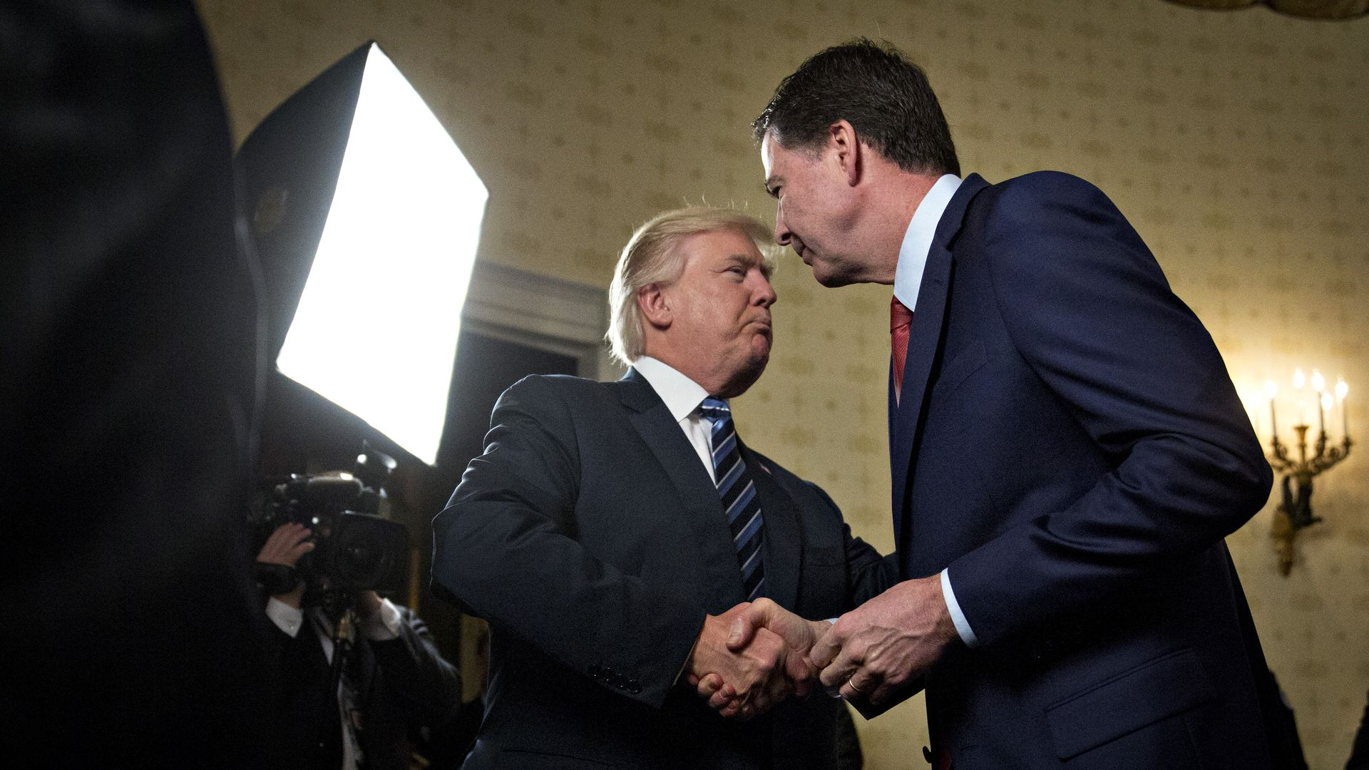 Donald Trump and James Comey shaking hands.
